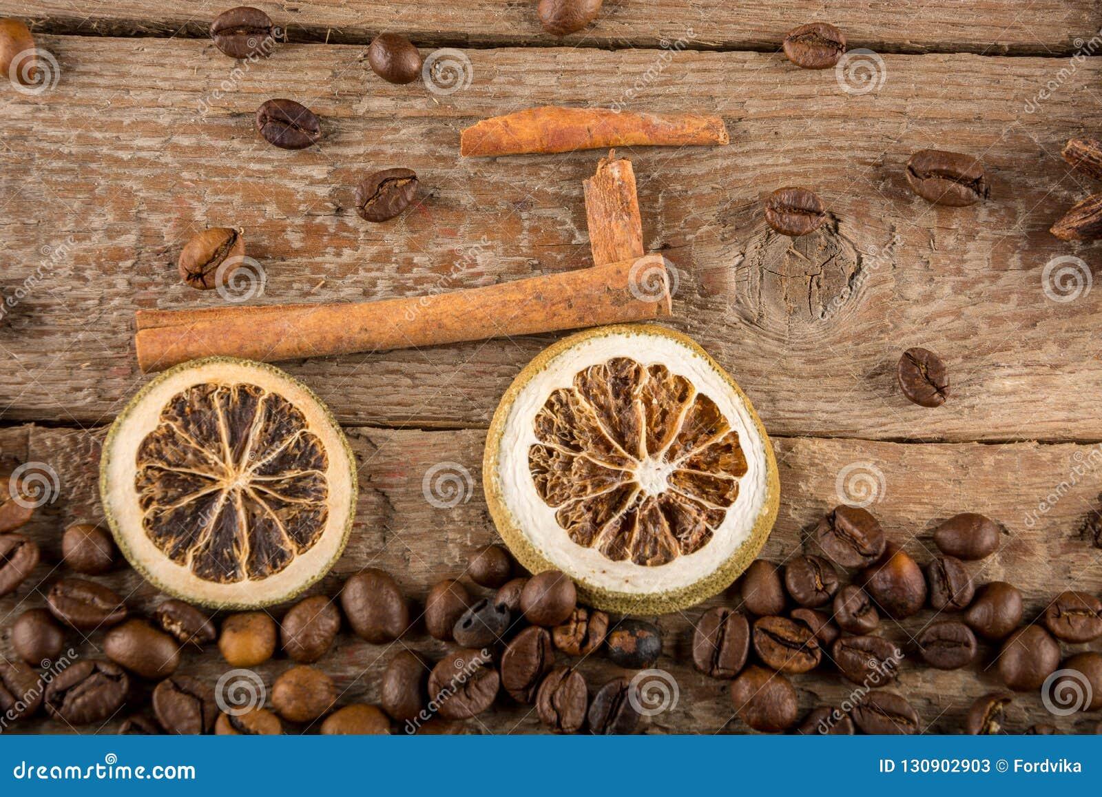 Uma bicicleta feita das partes de limões e de varas de canela secados, um trajeto feito dos feijões de café contra placas de made
