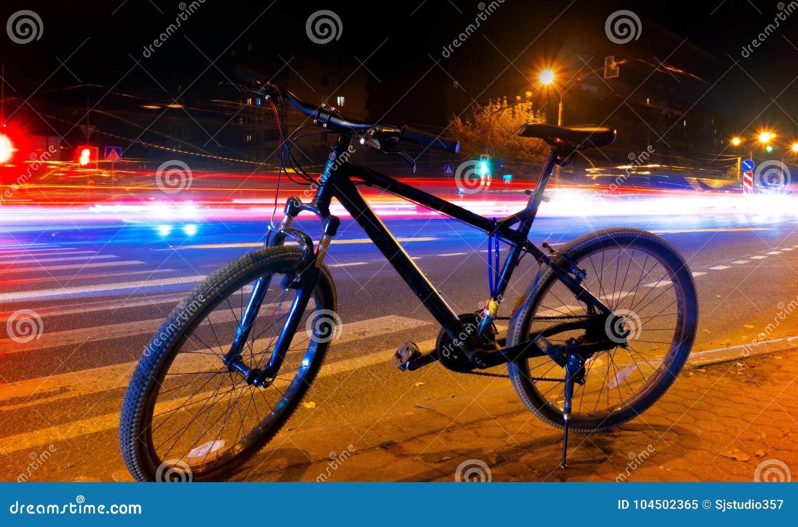 Uma bicicleta na rua em uma noite contra um fundo de luzes obscuras dos carros, a luz arrasta na rua