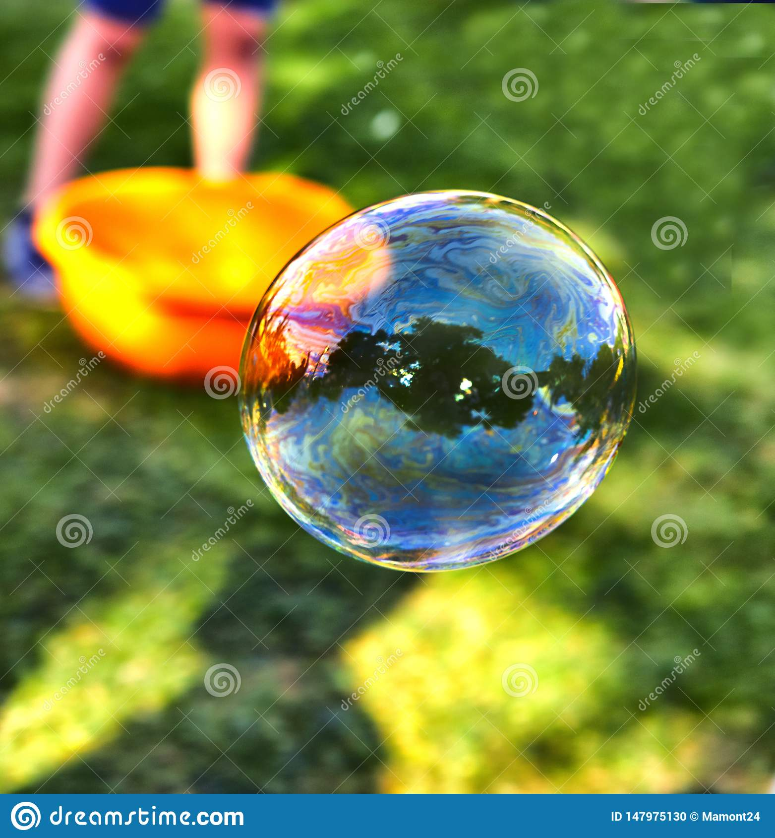 Uma bolha de sab?o voa na perspectiva da grama verde