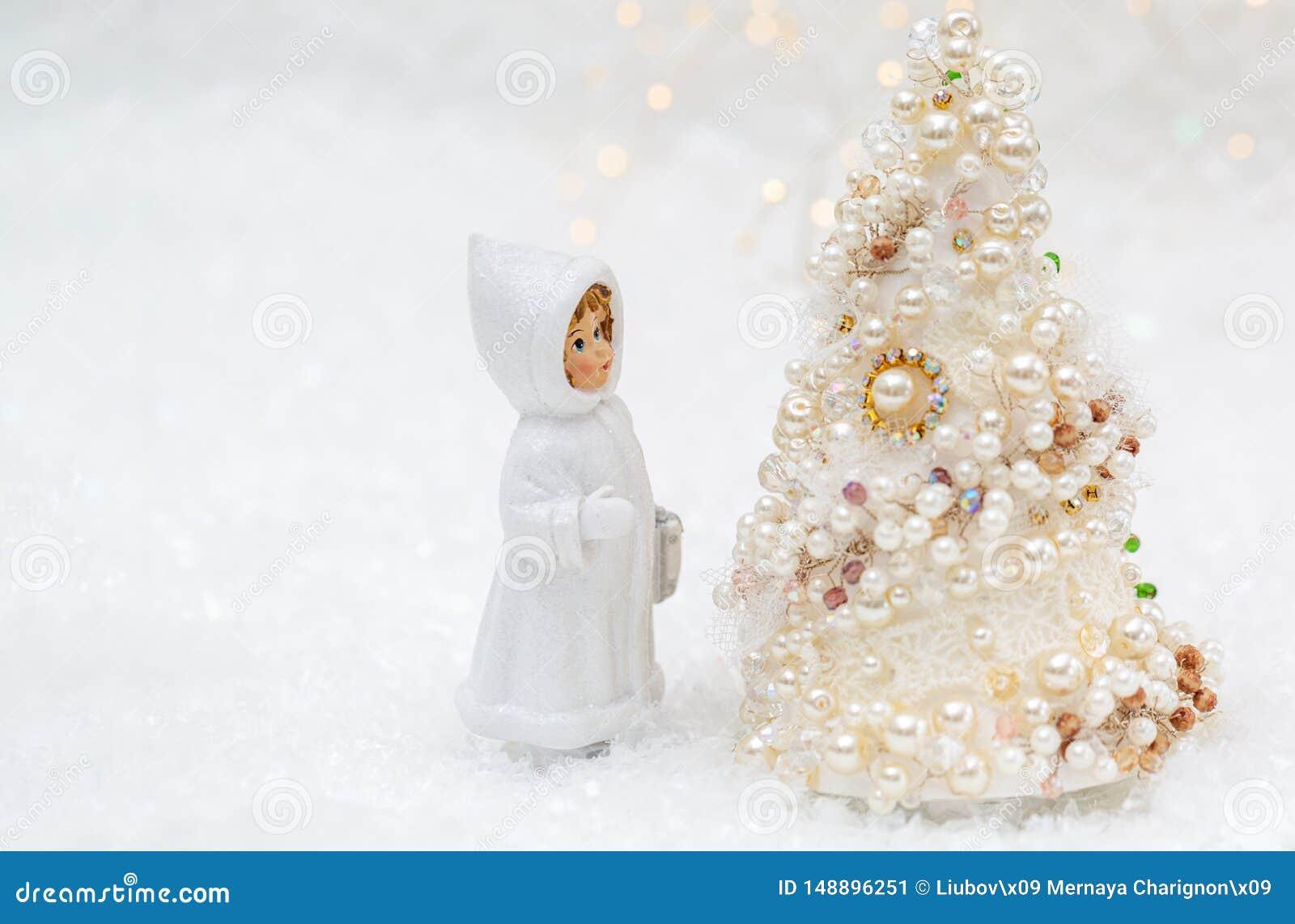 Uma boneca pequena na roupa do inverno est? olhando a ?rvore do ano novo ?rvore de Natal com p?rolas e fundo bonito do bokeh dos