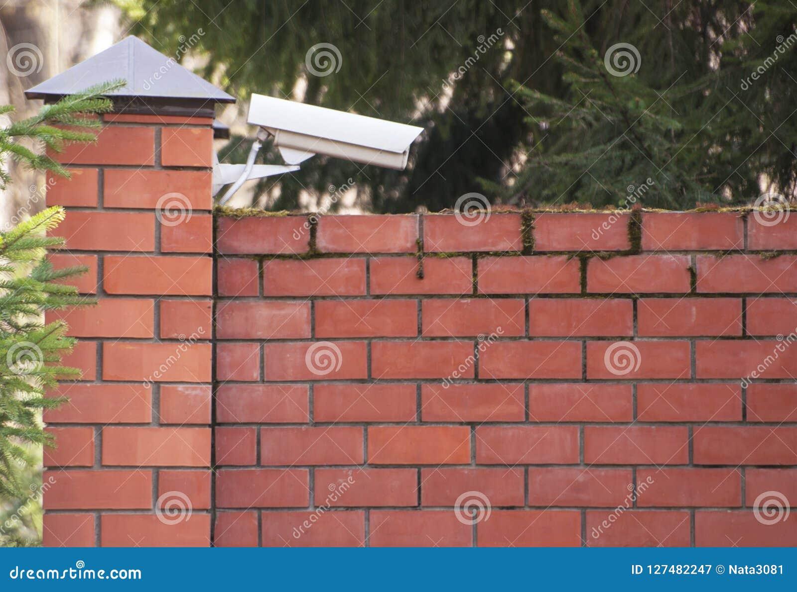 Uma câmara de vigilância externo sobre uma cerca do tijolo da propriedade privada Segurança de sistemas da segurança, fiscalizaçã