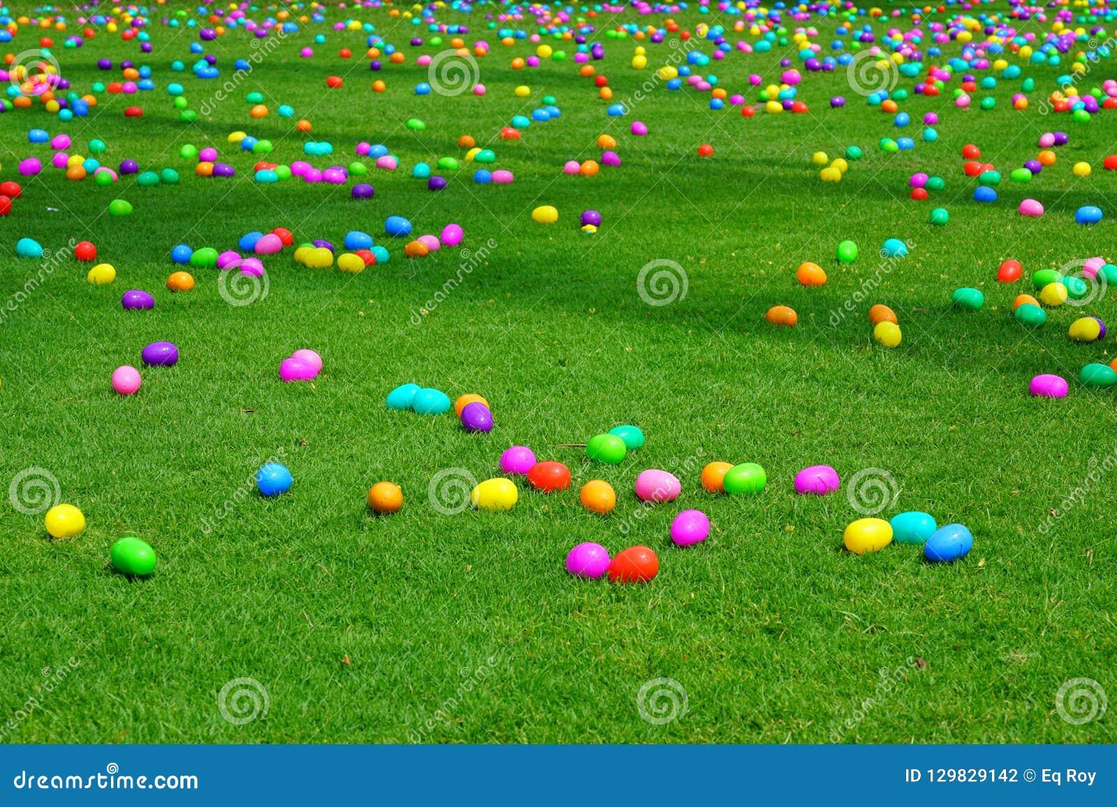 Uma caça do ovo da páscoa com ovos plásticos em um gramado verde
