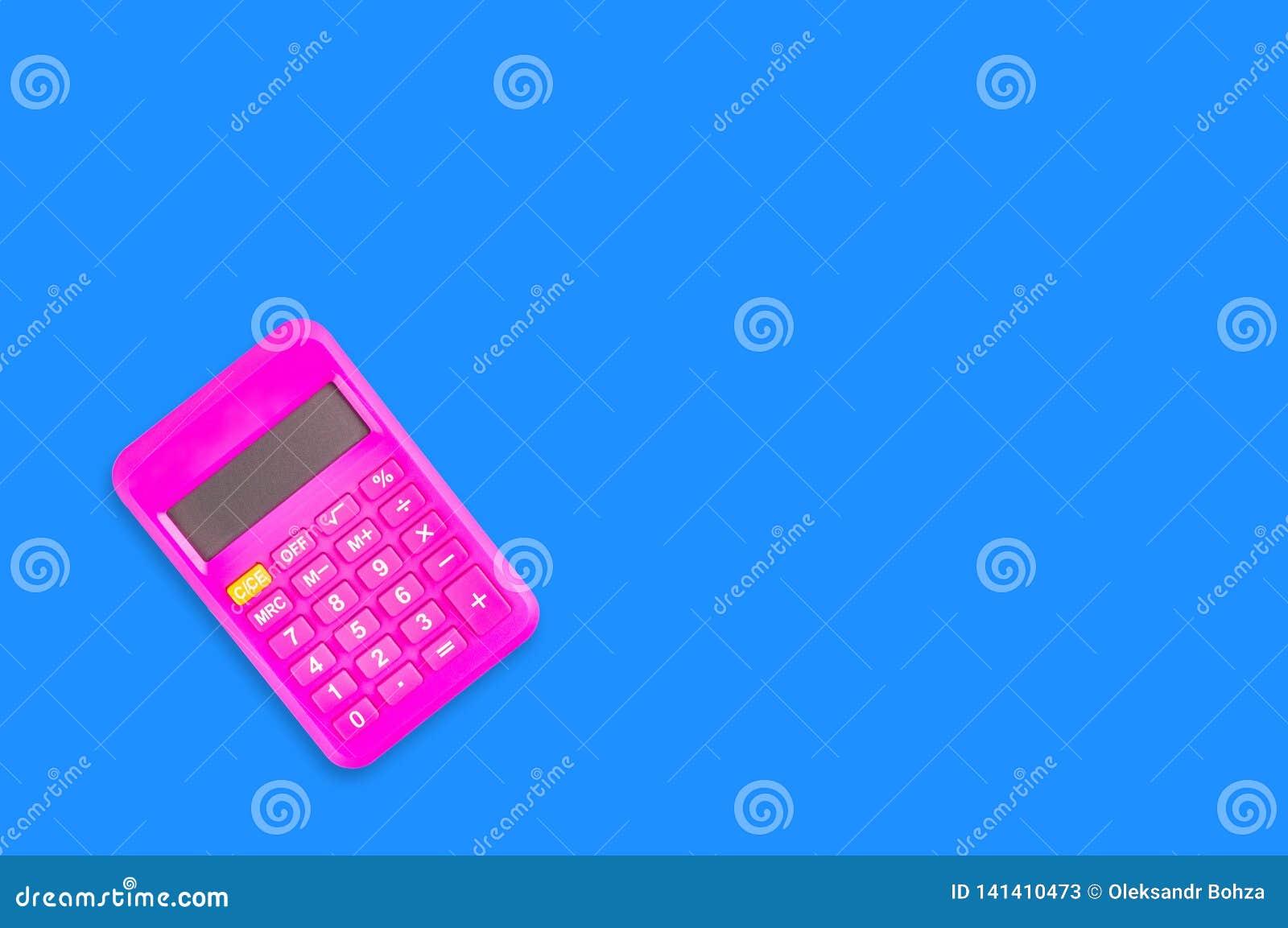 Uma calculadora plástica cor-de-rosa digital na tabela azul no escritório copie o espaço para seu texto Vista superior