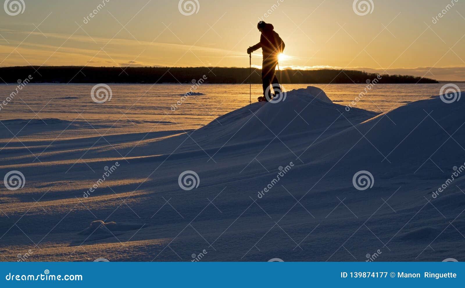 Uma caminhada do sapato de neve do por do sol em um lago congelado