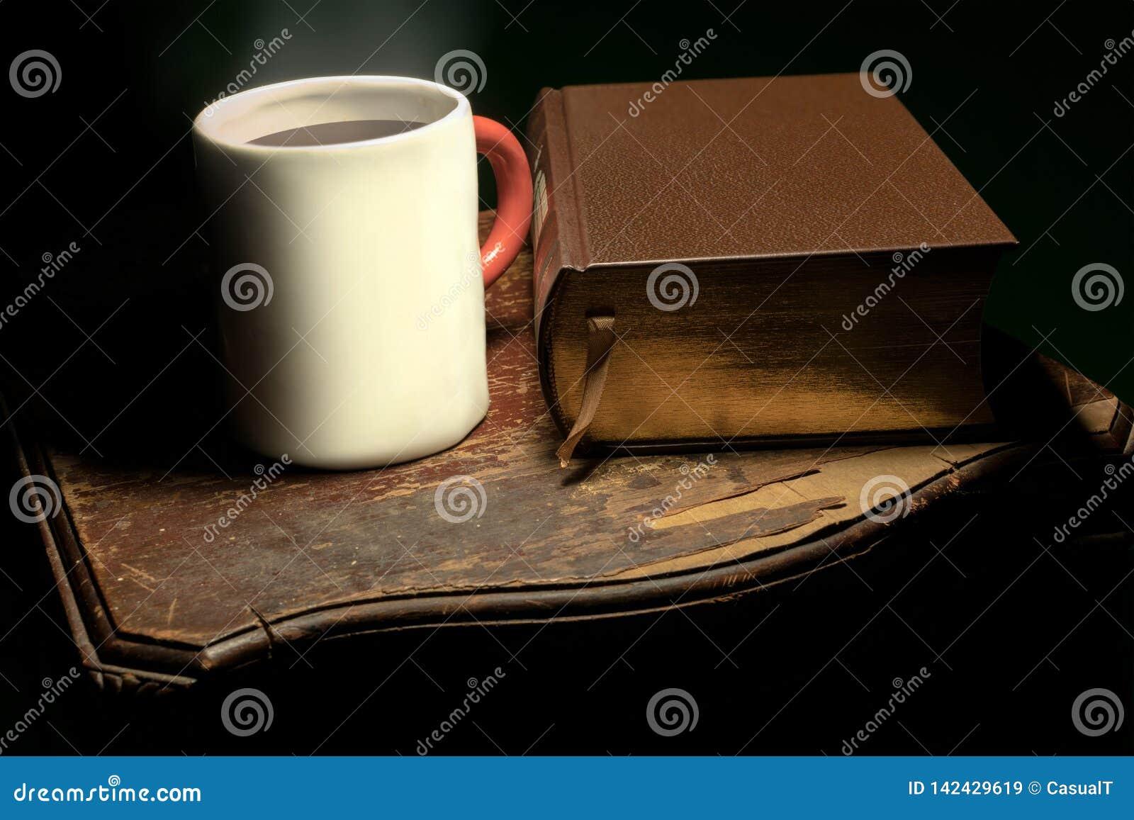 Uma caneca com cozinhar o chá ou o café quente colocado ao lado de um livro grande do couro-limite, em uma tabela de madeira velh