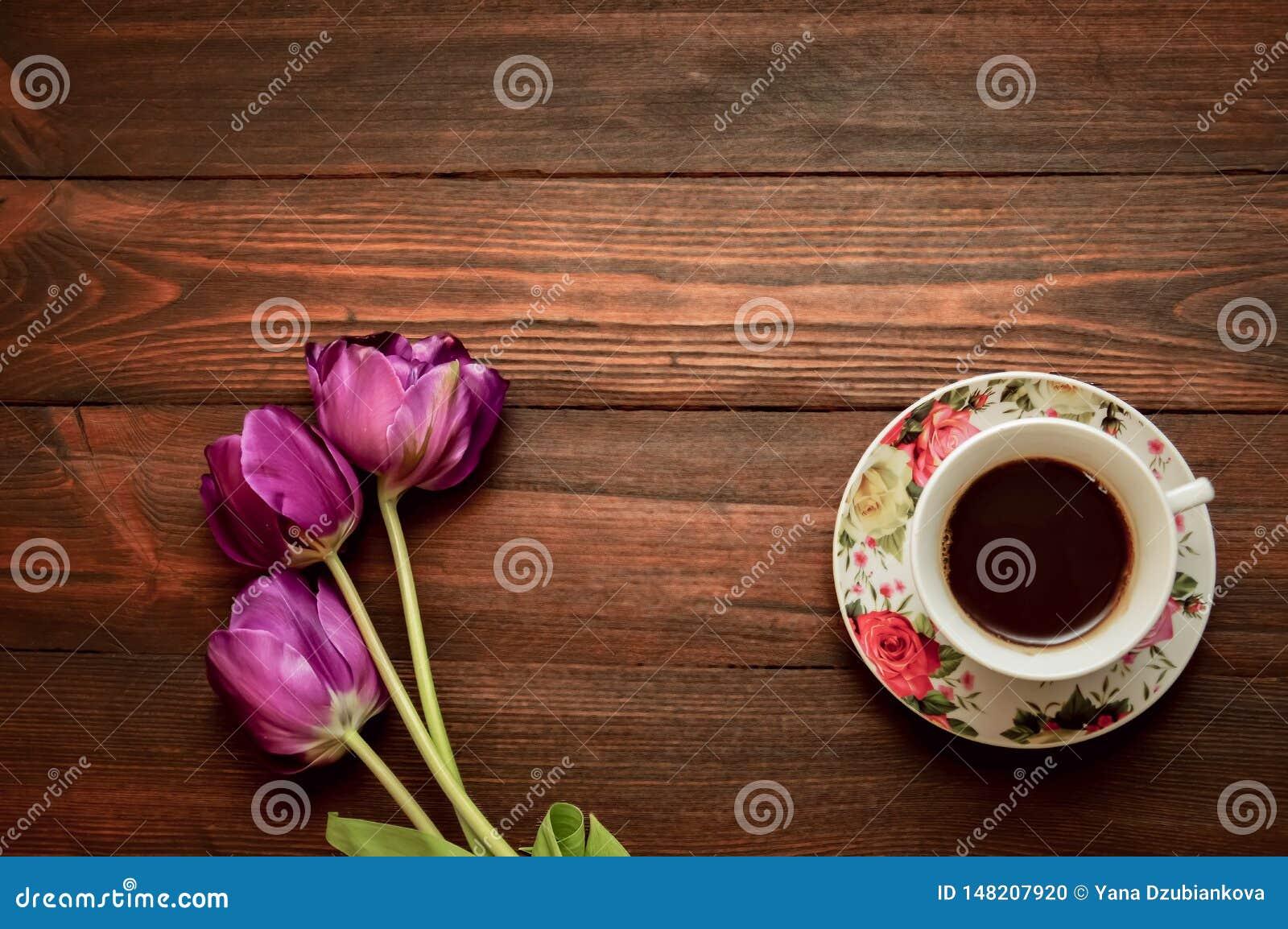 Uma x?cara de caf? ou um ch? em uns pires est?o em um fundo de madeira, tulipas roxas encontram-se em seguida