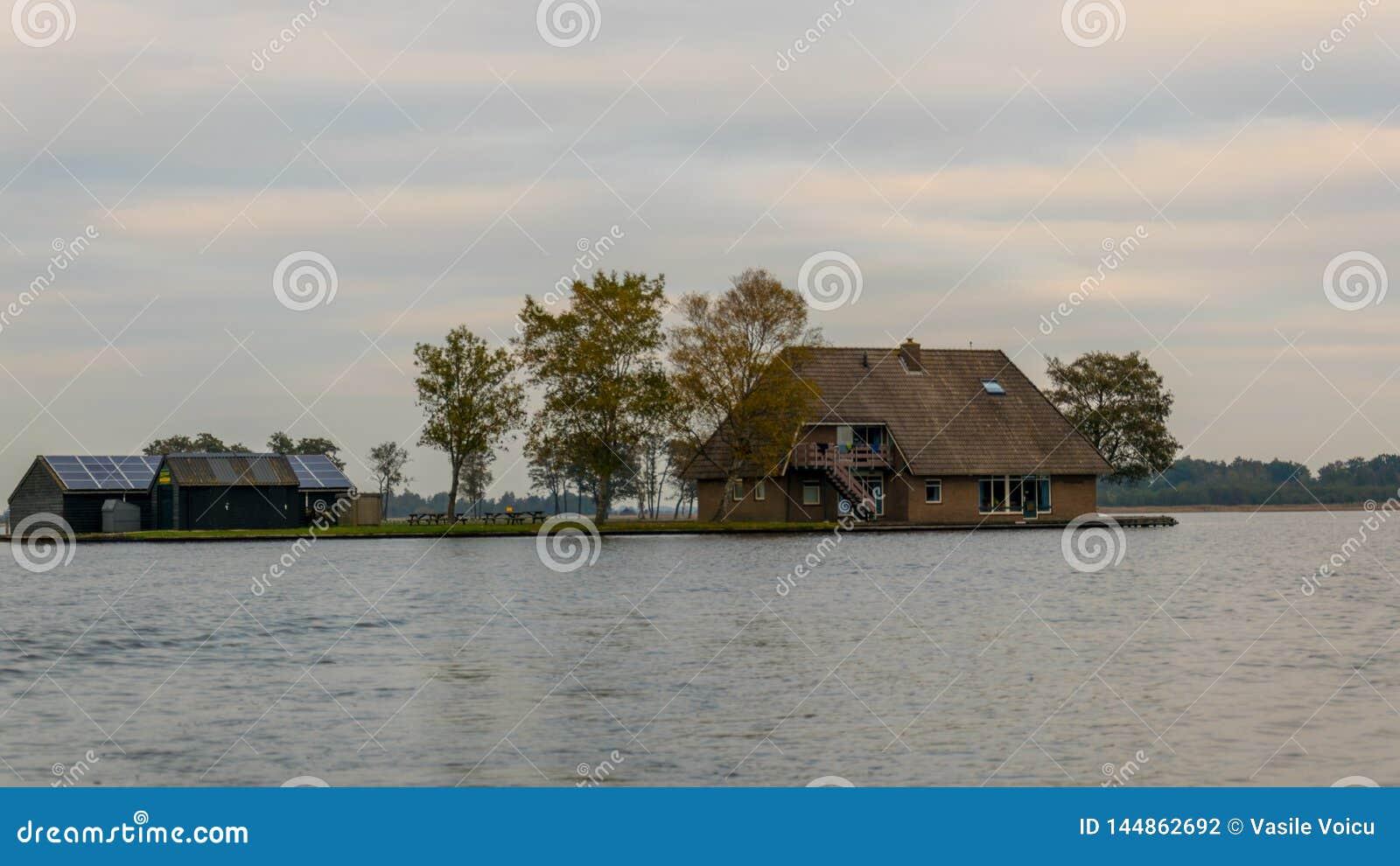 Uma casa em Giethoorn, nos Países Baixos, fotografados nos canais de água em um dia da queda, com grama verde, e arquitetura es