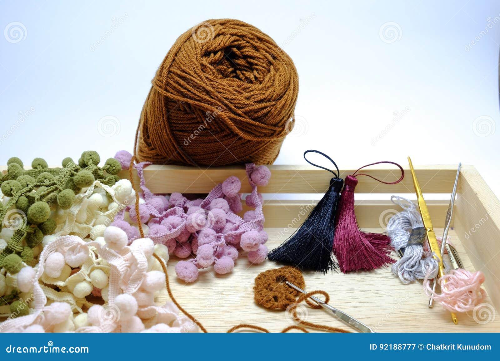 Uma cesta de faz crochê o fio, a borla e a agulha de crochê