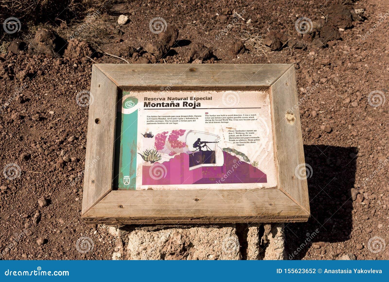 Uma chapa da informação ao lado do depósito do relógio na reserva natural especial da montagem vermelha, EL Medano, Tenerife, Esp