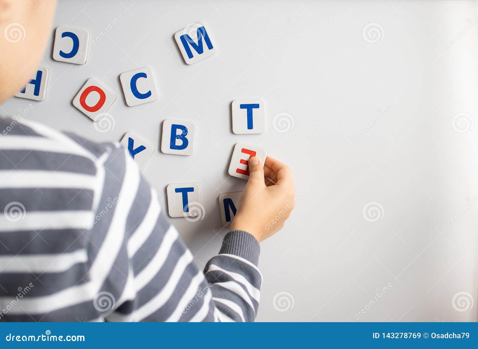 Uma criança aprende as letras no quadro-negro O menino está estudando as letras