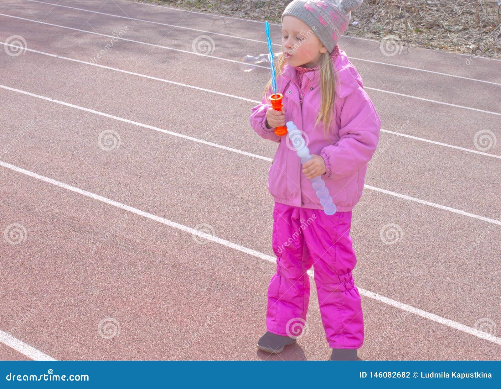 Uma criança com prazer e aplicação infla bolhas