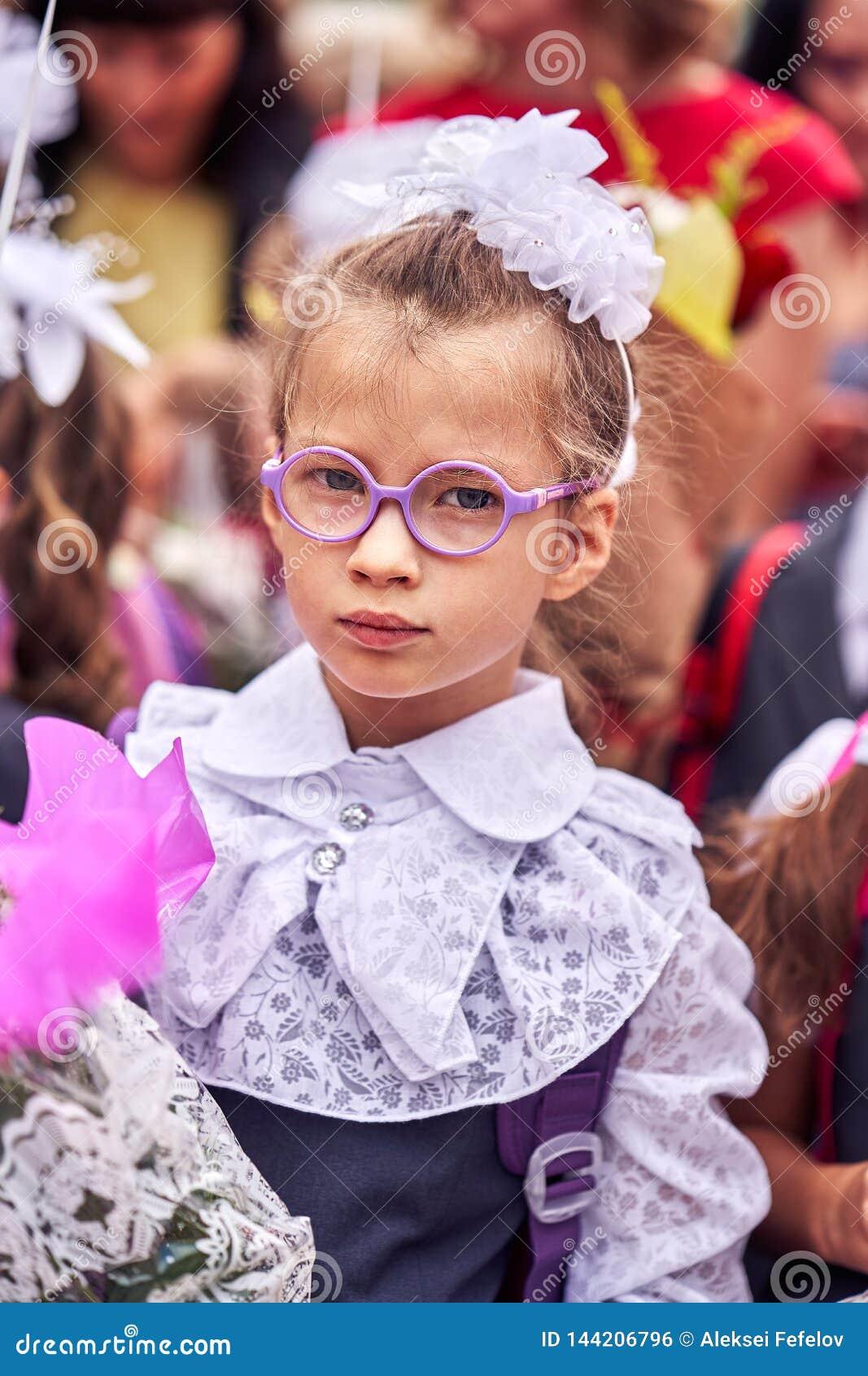 Uma criança da menina no uniforme festivo da escola com curvas, vidros e um saco de escola nela para trás está estando em uma mul