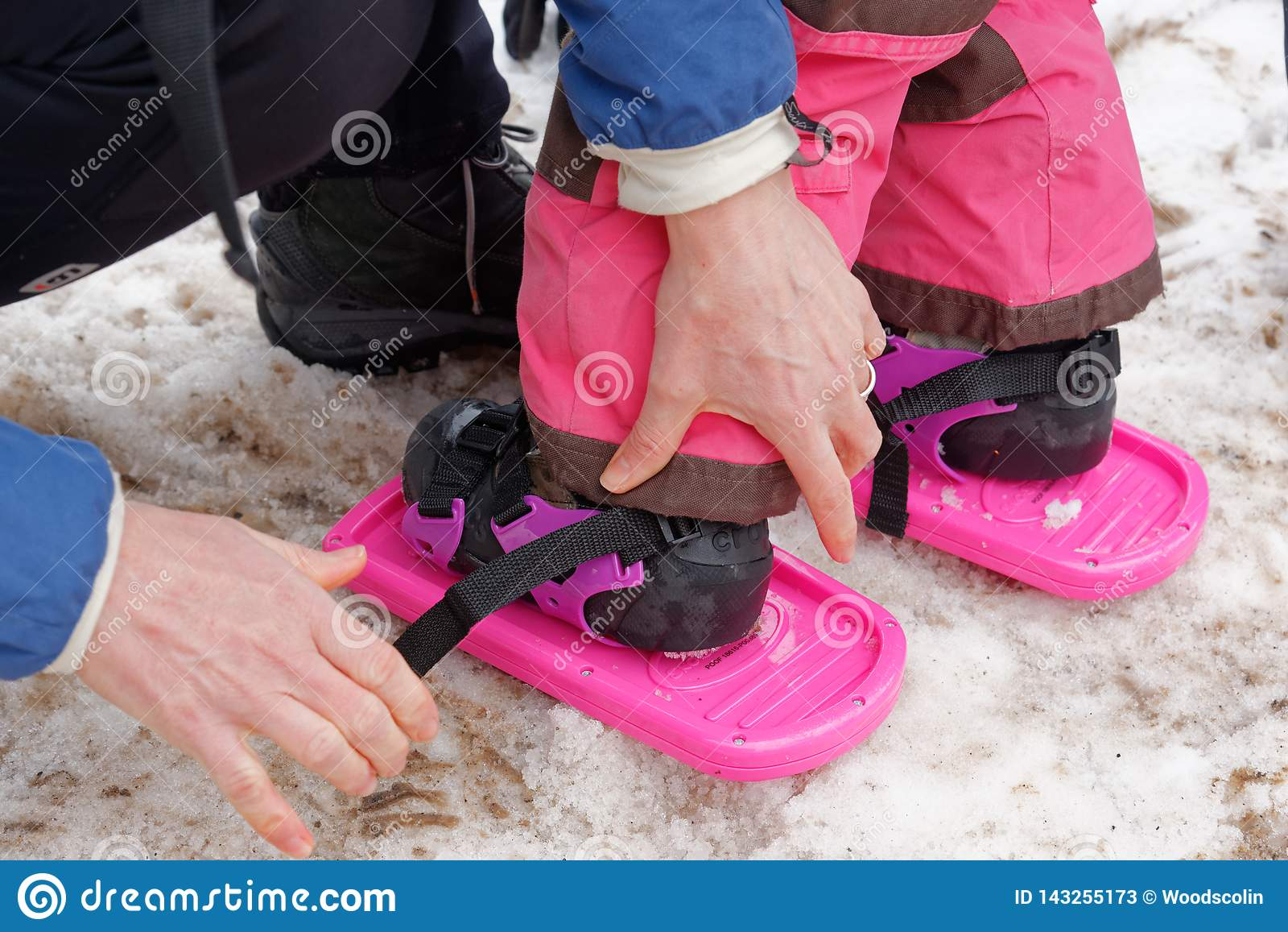 Uma criança de 3 anos da menina que tem o sapatos de neve unidos