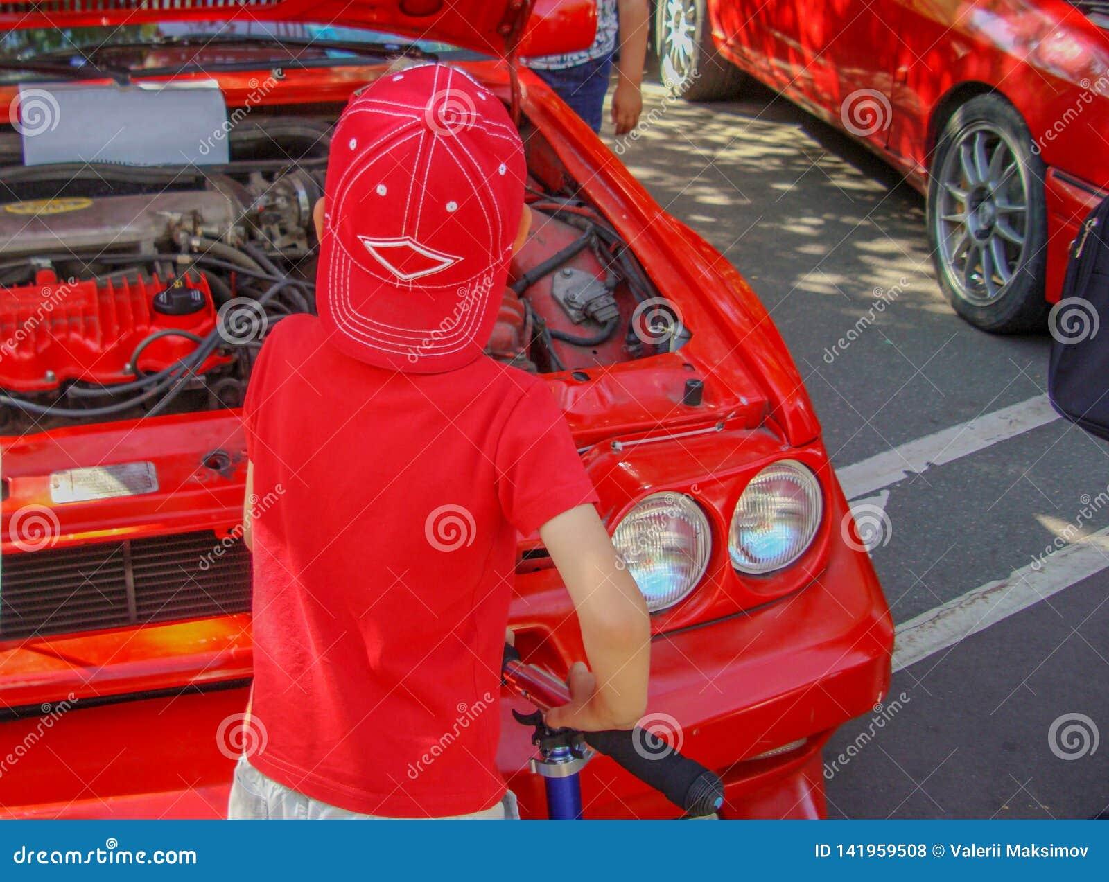 Uma criança na roupa vermelha examina o motor do carro