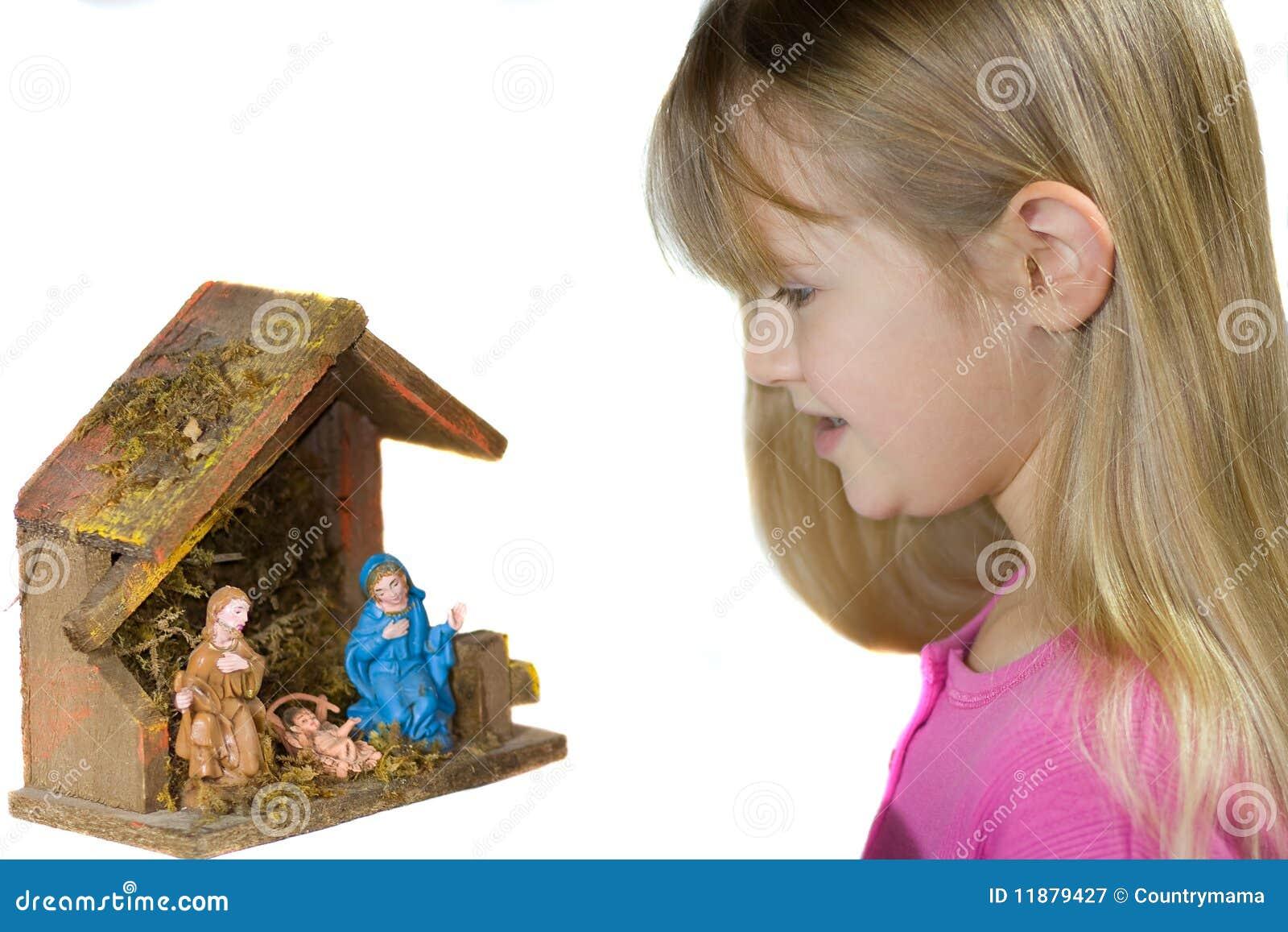 Uma criança que olha uma natividade do Natal.