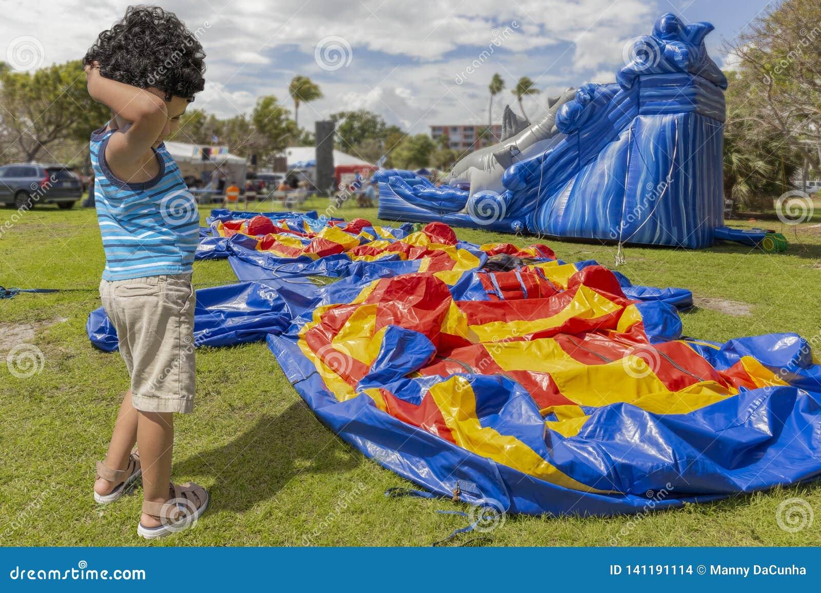 Uma criança risca sua cabeça quando estiver ao lado de uma casa desinflada do salto