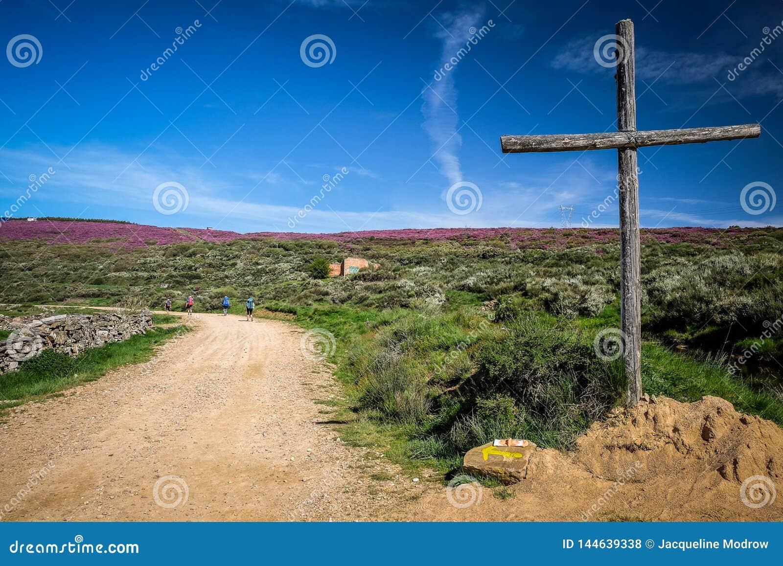 Uma cruz que marca a maneira no trajeto de Camino Frances a Santiago de Compostela