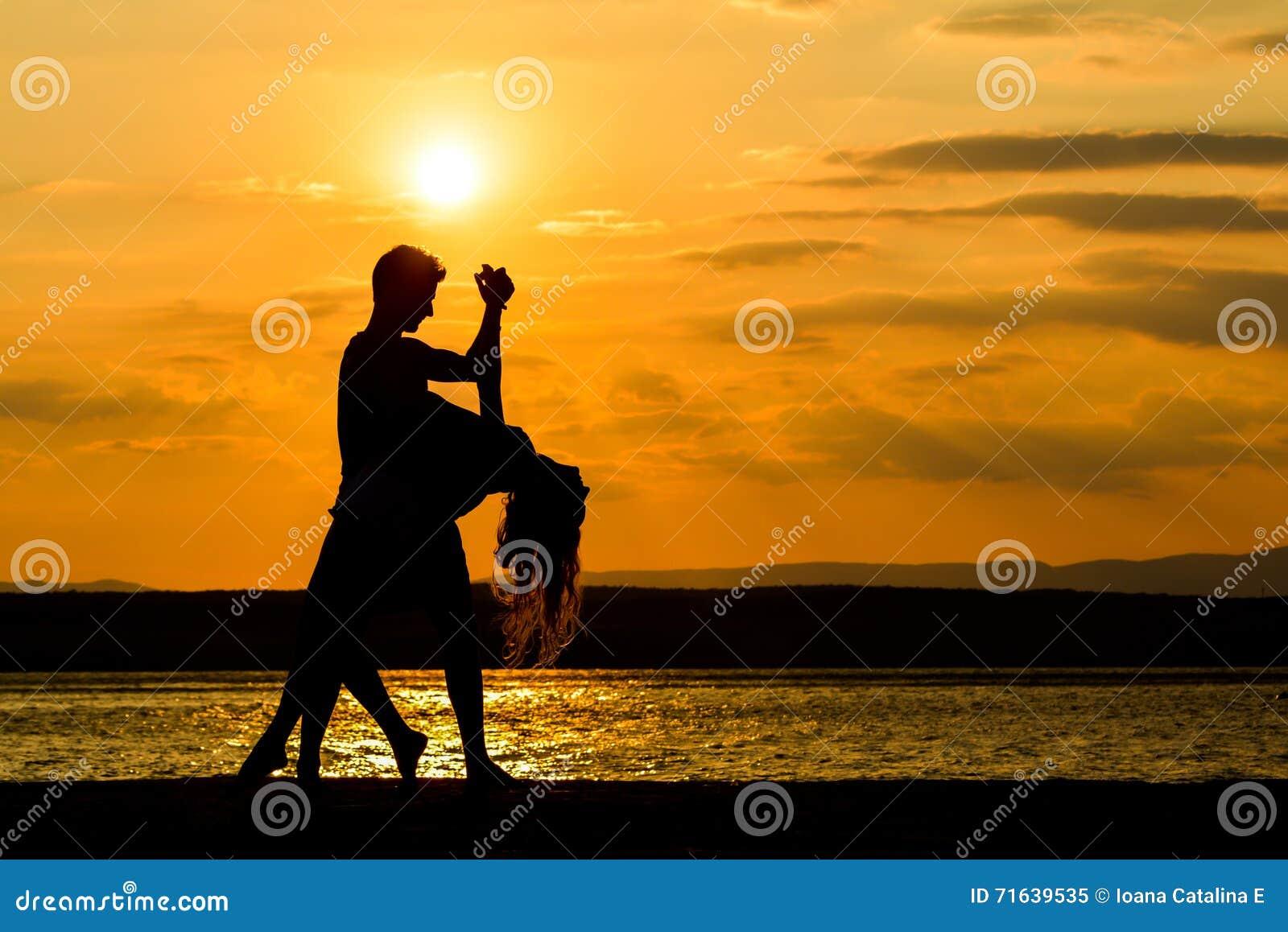 Uma dança dos pares pelo mar no por do sol