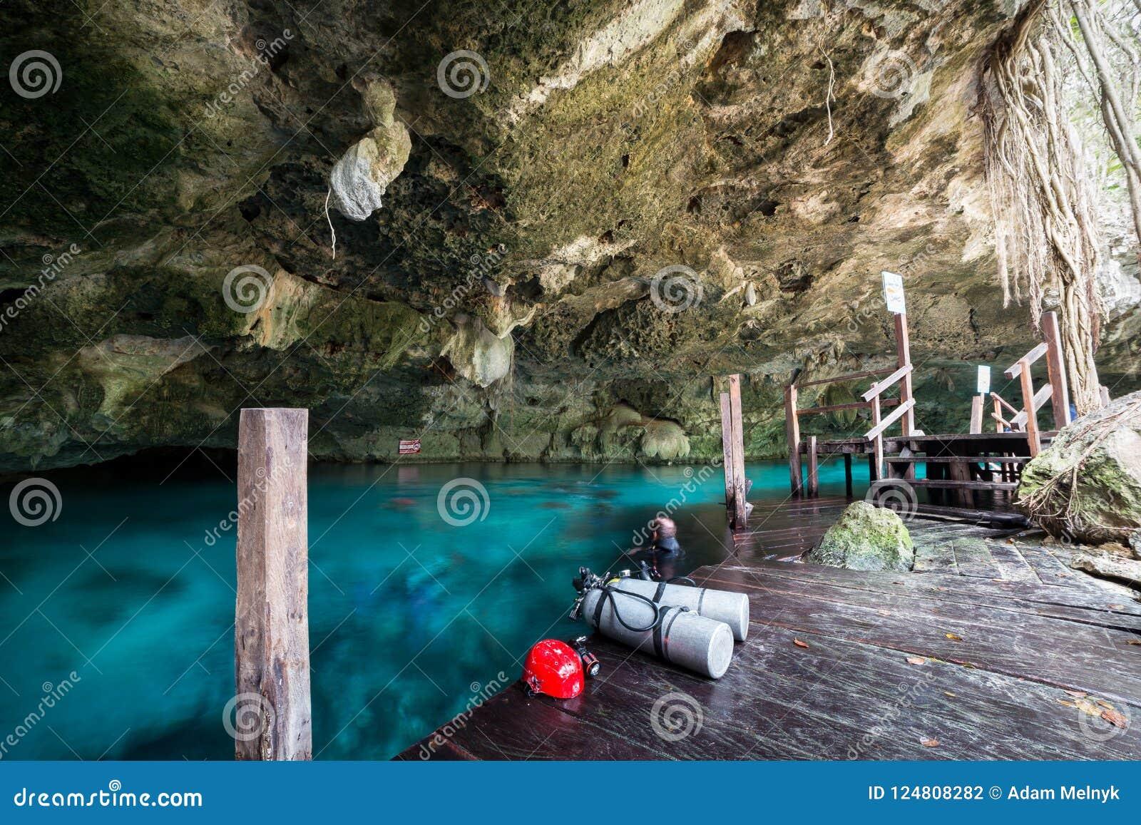 Uma das entradas da caverna ao cenote de Dos Ojos perto de Tulum, México com o mergulhador borrado para fora