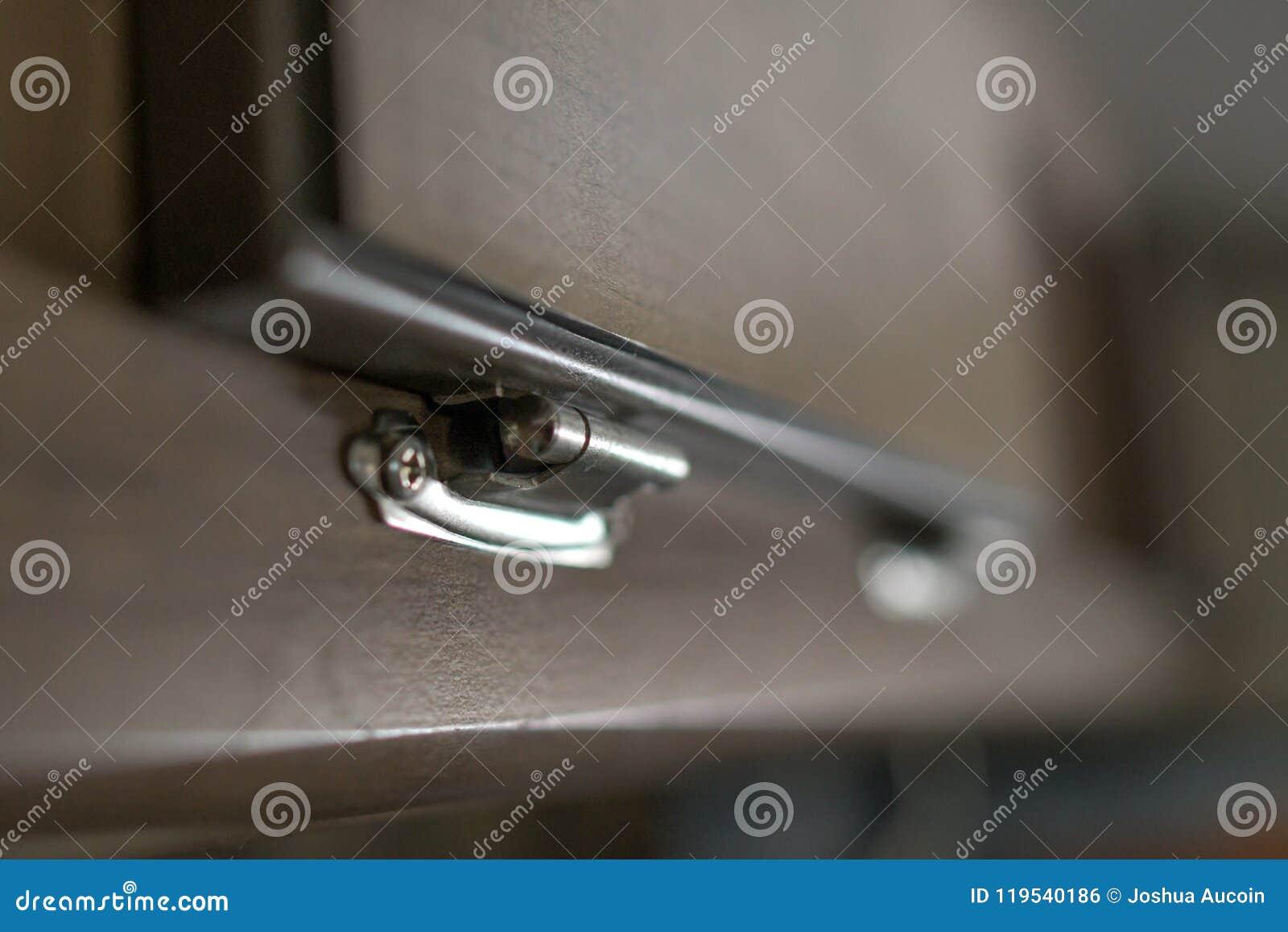 Uma dobradiça de prata minúscula que conecta um painel de madeira a uma cara do armário que faz uma porta pequena