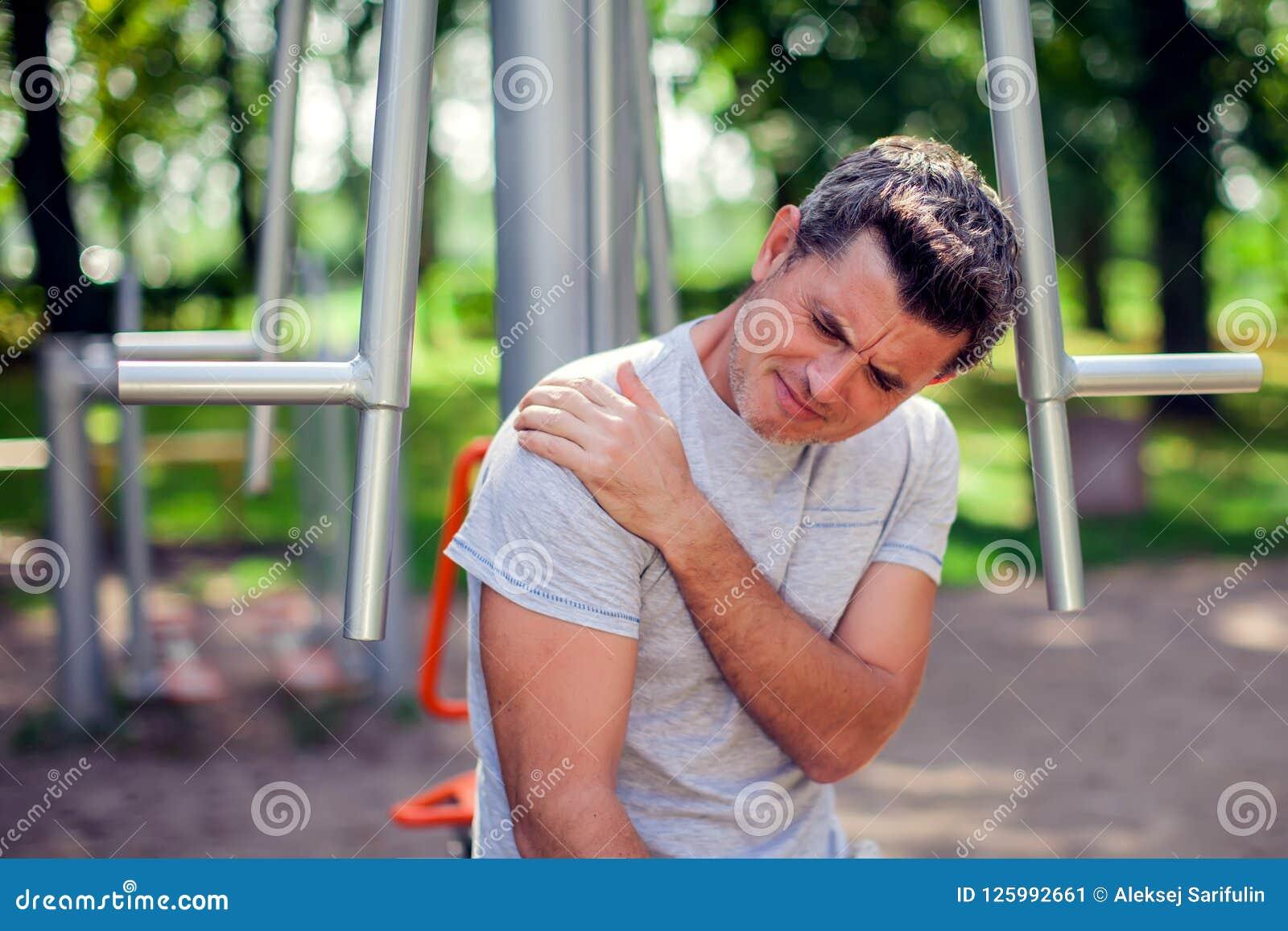Uma dor do sentimento do homem em seu ombro durante o esporte e exercício em t