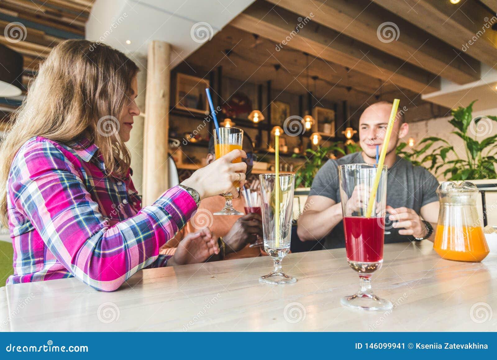 Uma empresa dos jovens que t?m o divertimento, bebidas bebendo, cocktail, sucos em um caf? melhores amigos da reuni?o