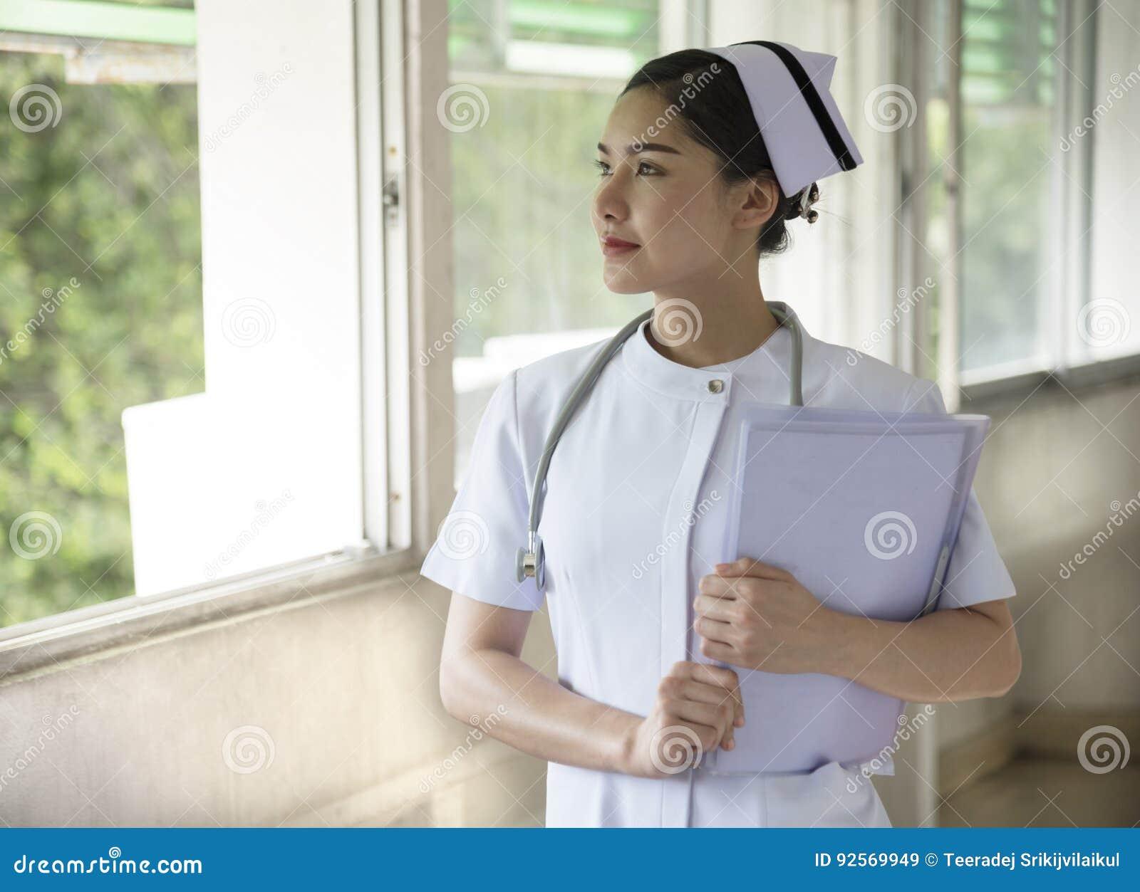Uma enfermeira bonita guarda o informe médico