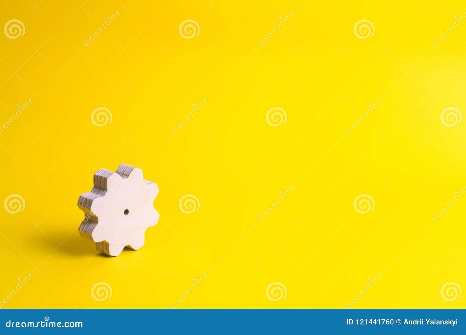 Uma engrenagem de madeira em um fundo amarelo O conceito da tecnologia