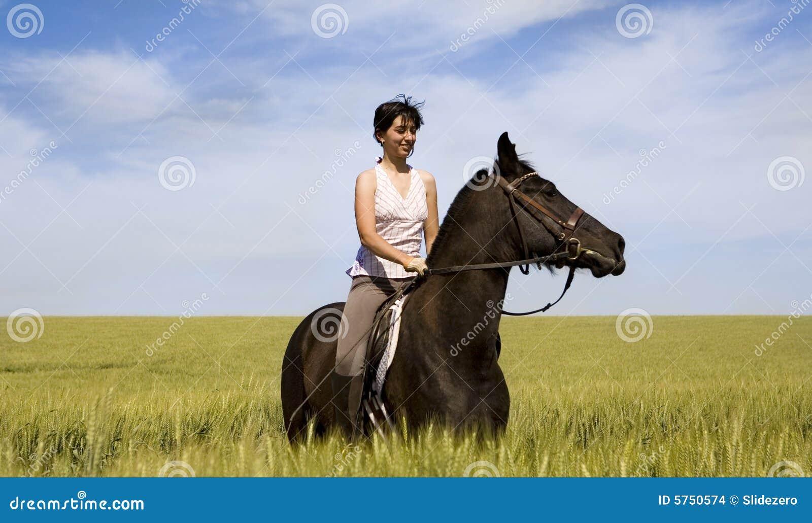 Uma equitação fêmea em um cavalo preto