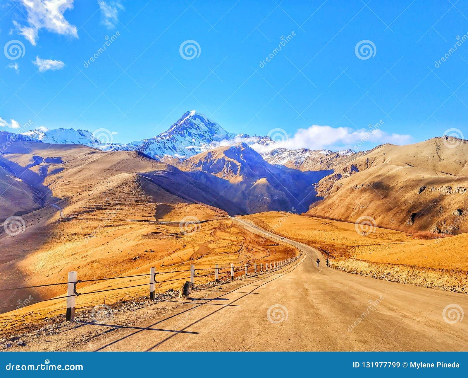 Uma estrada à montanha neve-tampada