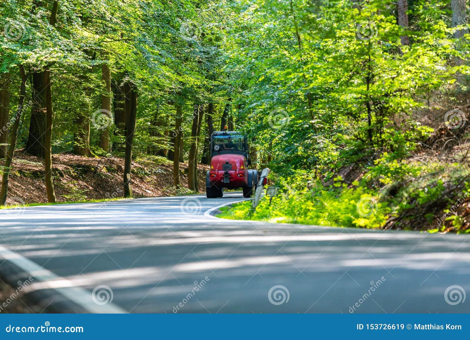 Uma estrada secundária perigosa em uma floresta da rena apenas que chove canivetes assim em Alemanha