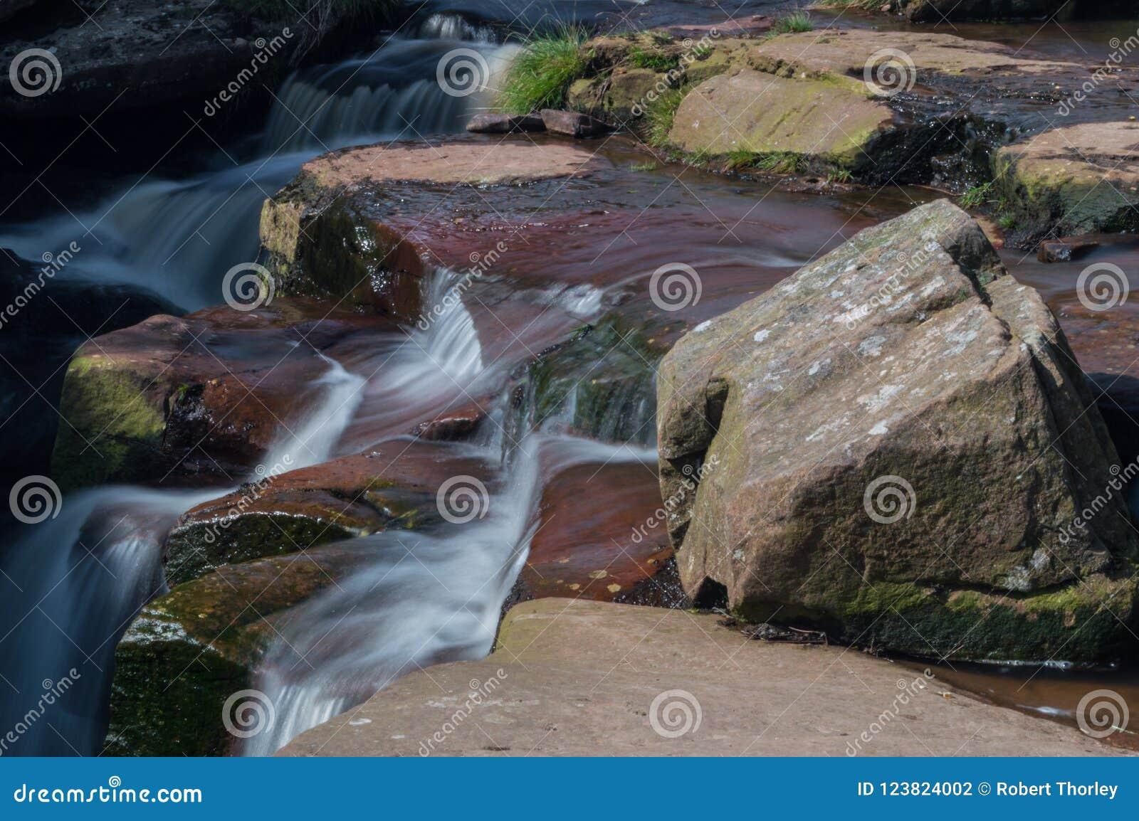 Uma exposição longa da cascata pequena da cachoeira sobre rochas verdes e marrons