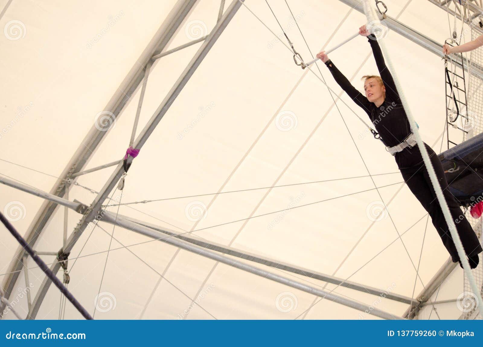 Uma fêmea adulta pendura em um trapézio de voo em um gym interno A mulher é um artista de trapézio amador
