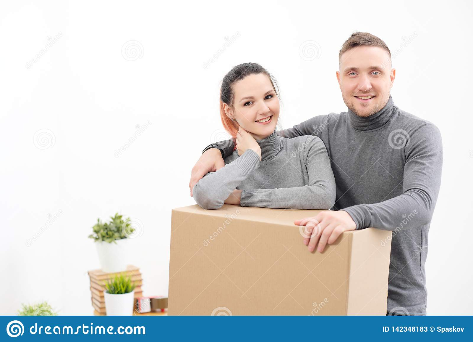 Uma família nova, um homem e uma mulher em camisetas cinzentas estão movendo para apartamentos novos Caixas com carga em um branc