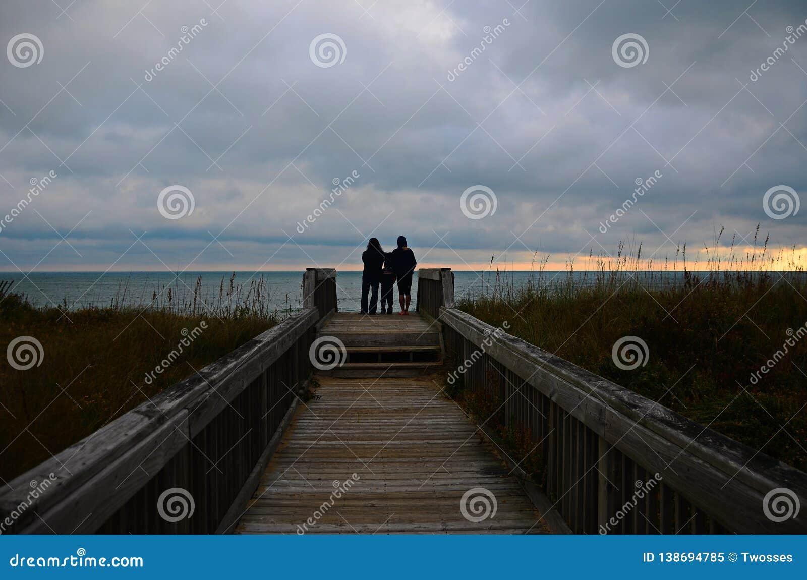 Uma família olha um nascer do sol na praia