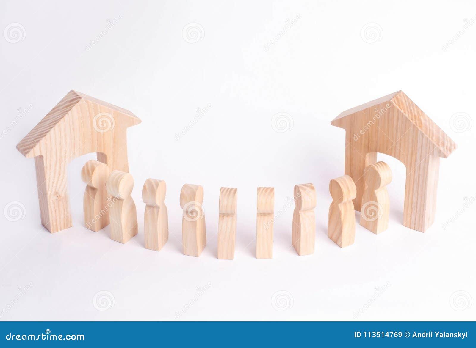 Uma figura de madeira de um homem encontra um convidado em um fundo branco Casa de madeira O conceito de uma casa de apartamento,