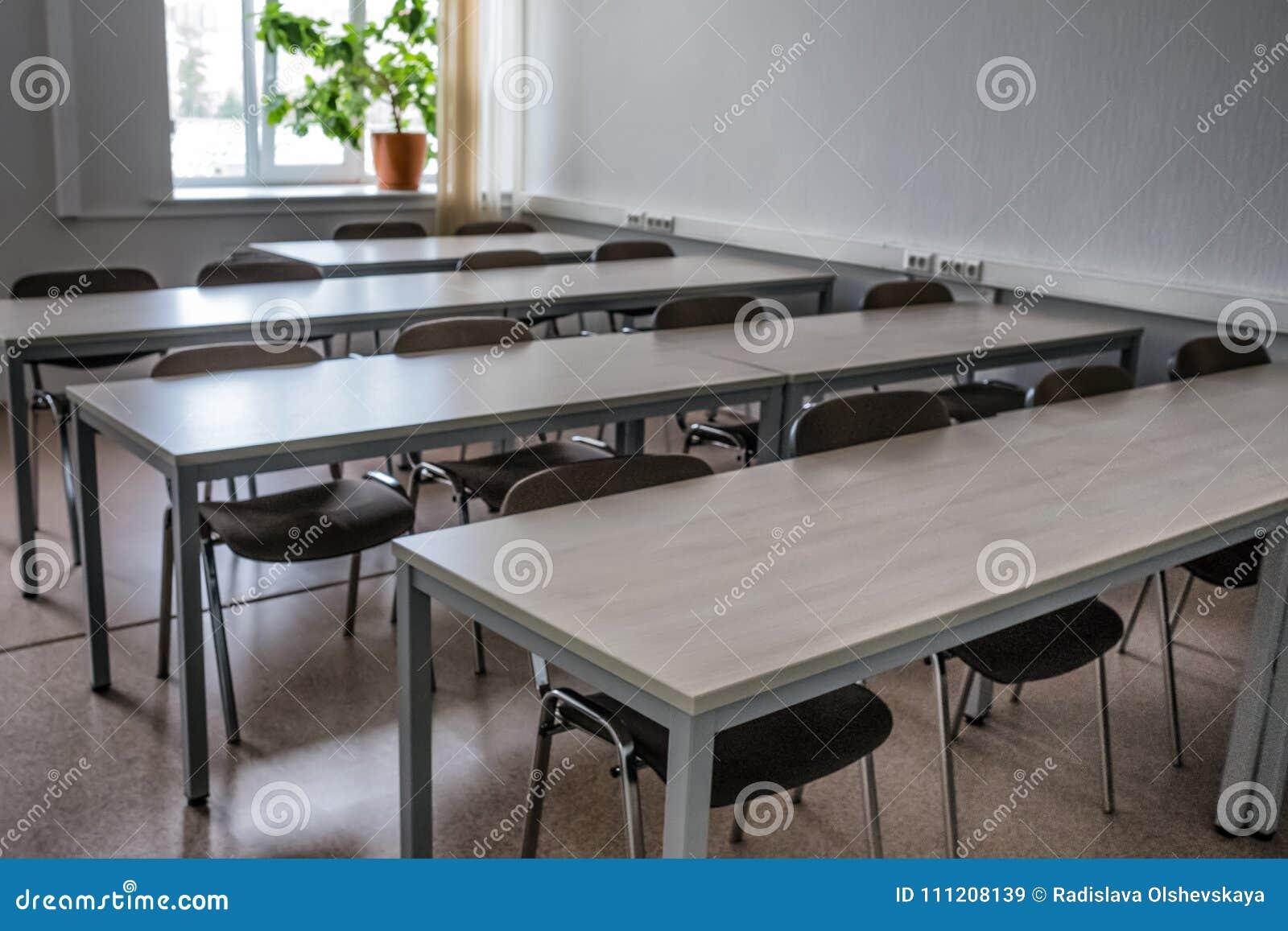 Uma fileira das tabelas e das cadeiras em uma sala de aula