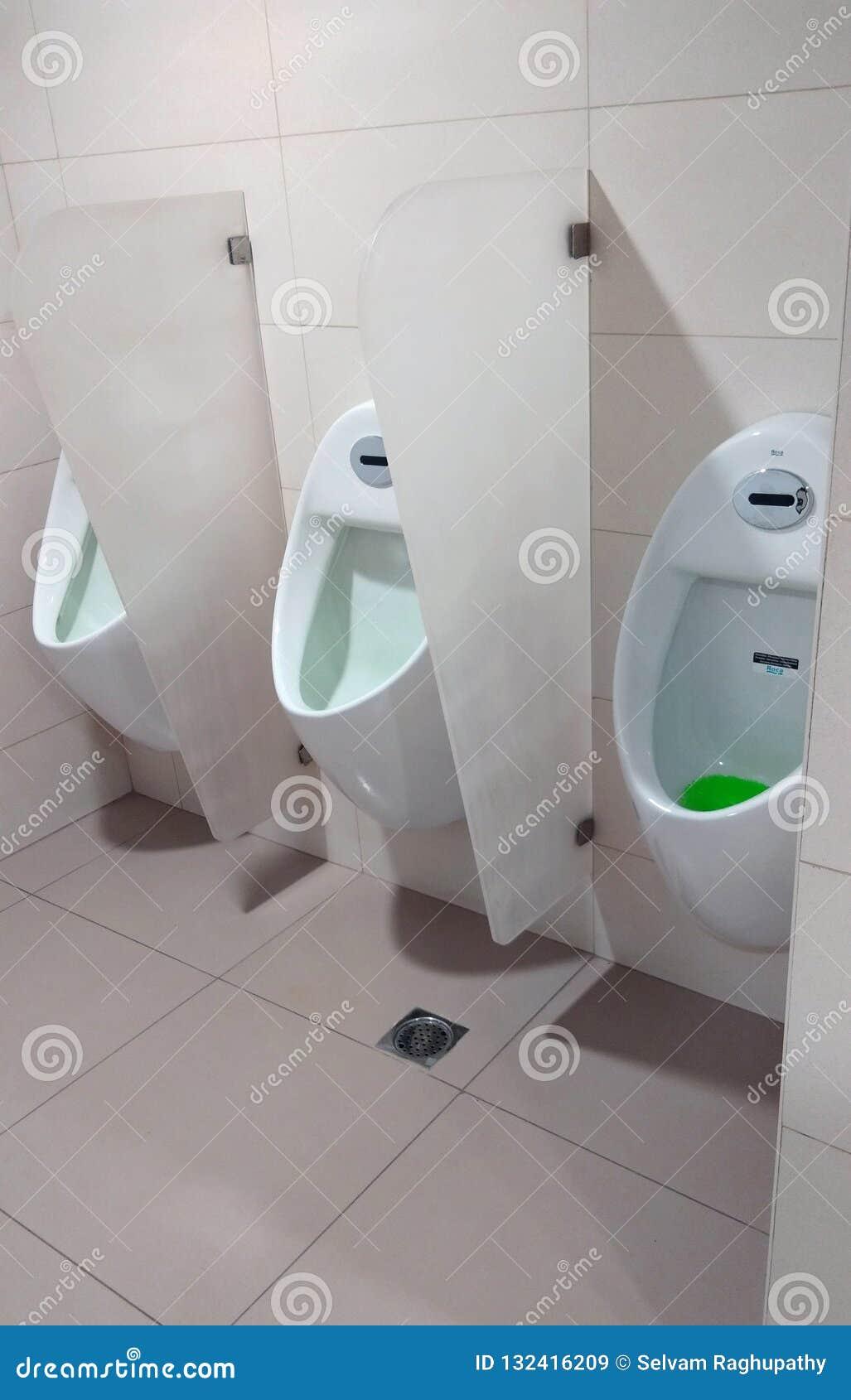 Uma fileira de um interior moderno do toalete com mictório
