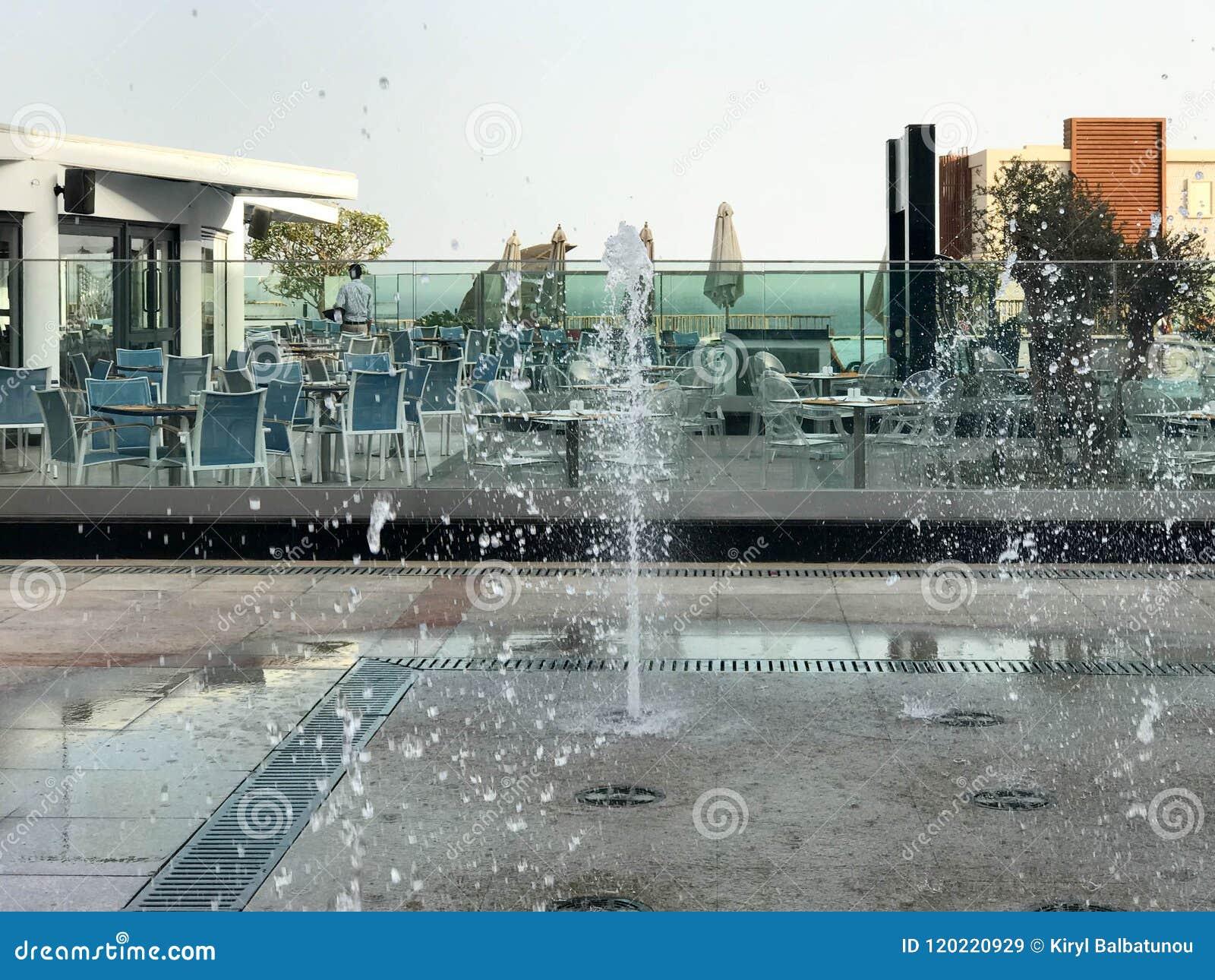 Uma fonte bonita pequena do canto no ar livre, na rua Gotas da água, jatos da água congelados no ar em voo