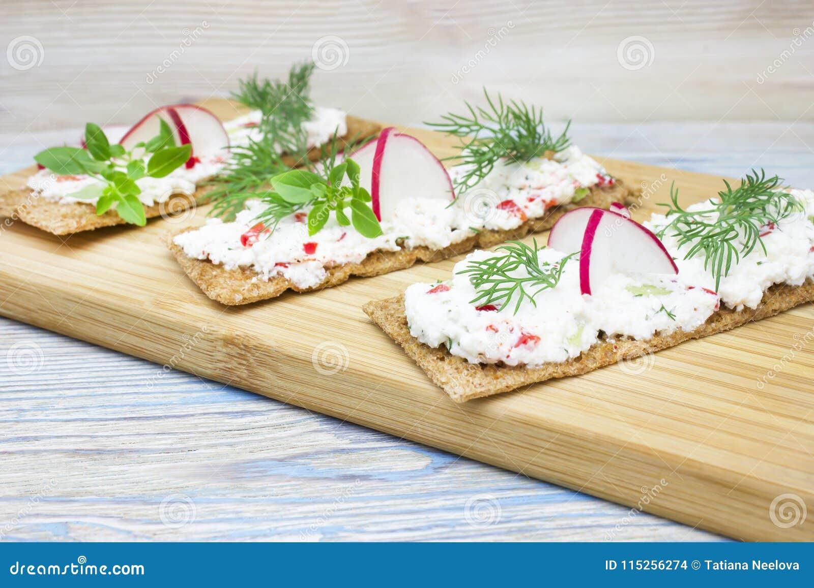 Uma foto dos biscoitos, do brinde torrado do pão de centeio com o requeijão decorado com rabanete, do pepino, do aneto e da manje