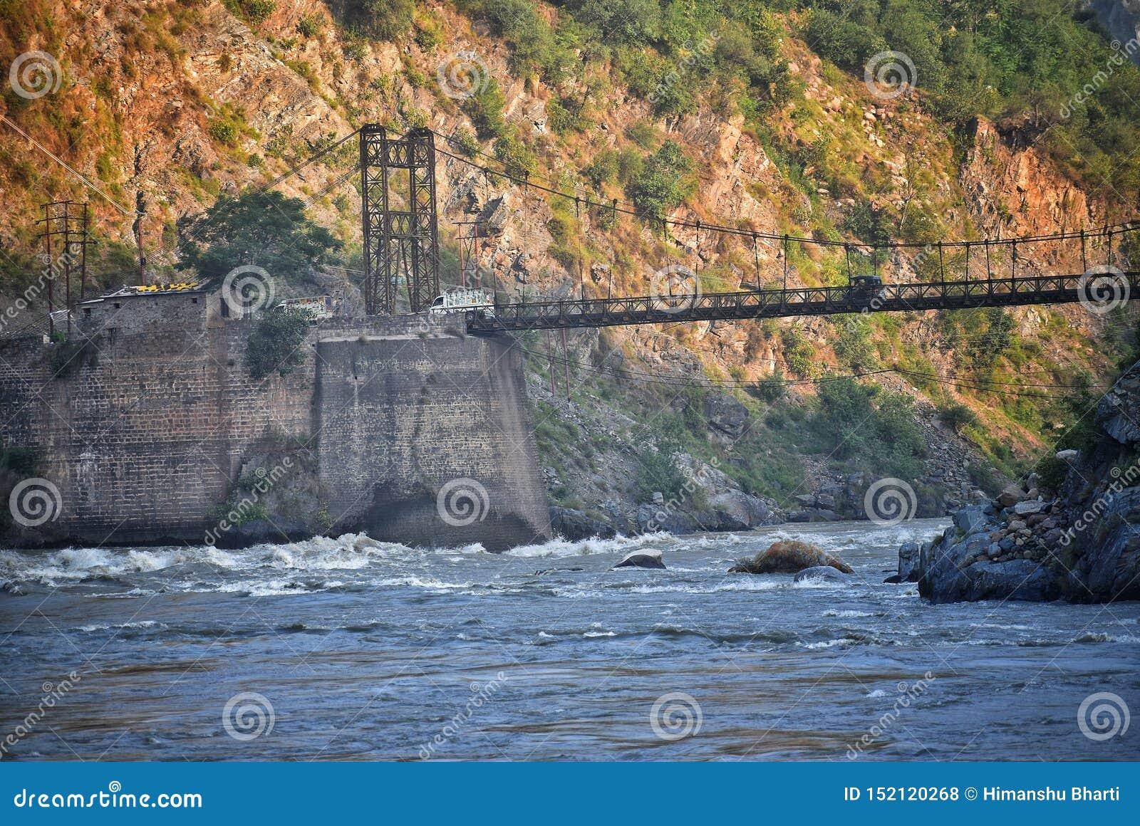 Uma fotografia de um ferro e de uma ponte de madeira sobre um rio com a montanha no fundo que bate por raios de sol cedo na manhã