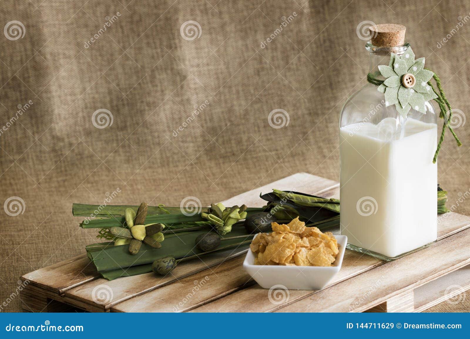 Uma garrafa de vidro com leite fresco e uma decoração floral