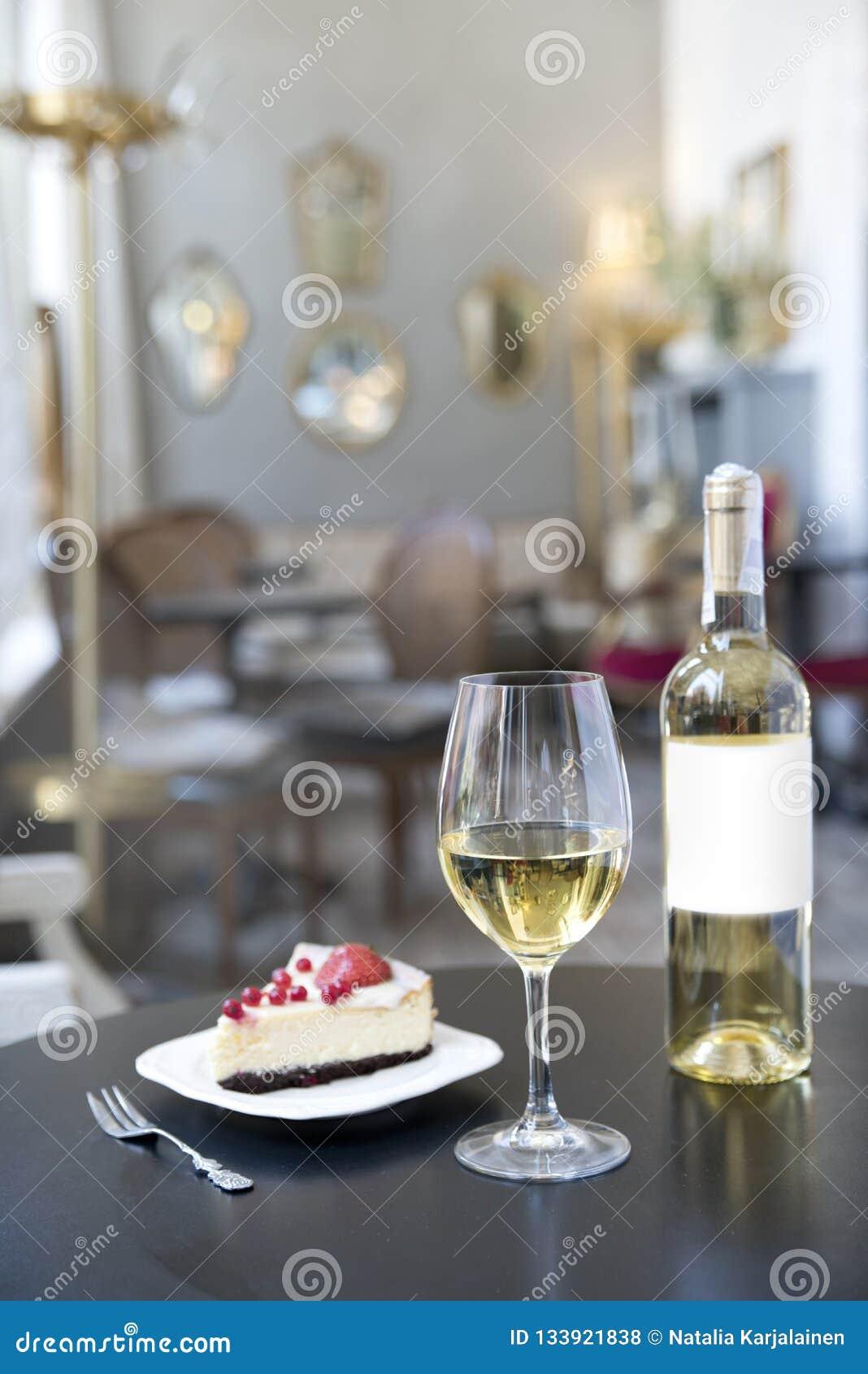 Uma garrafa do vinho branco, de um vidro e de um bolo no fundo de um café do vintage