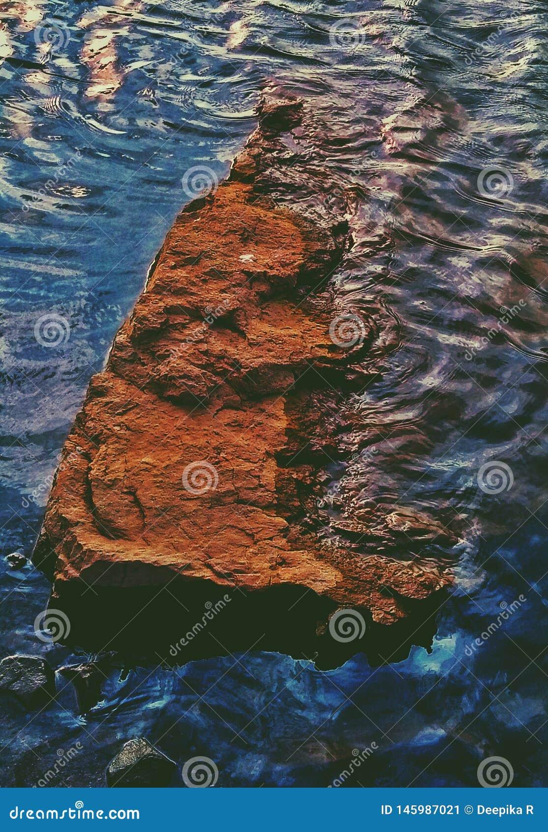 Uma imagem artística bonita de uma rocha em uma água