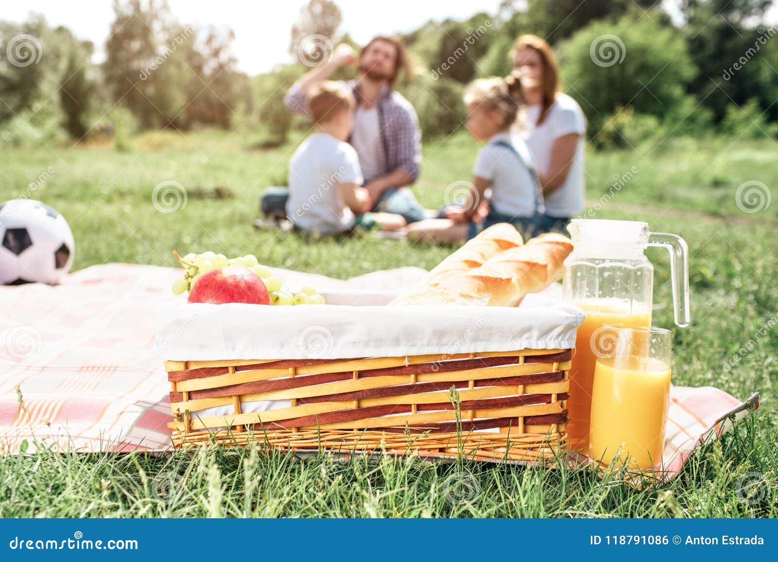 Uma imagem da cesta com o fruto e o pão que estão na cobertura na grama Há um frasco grande do suco de laranja além dele