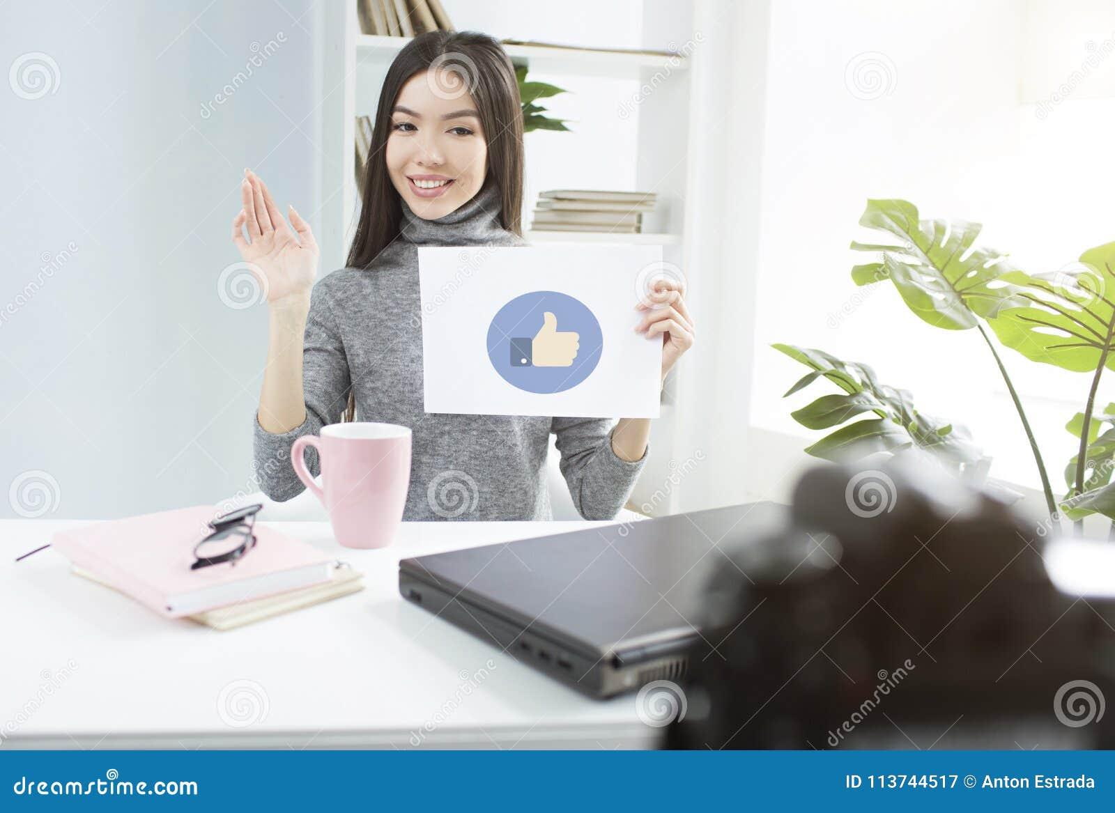 Uma imagem da menina bonita que gosta quando seus seguidores gostarem de seu vídeo Está sentando-se na tabela e está guardando-se