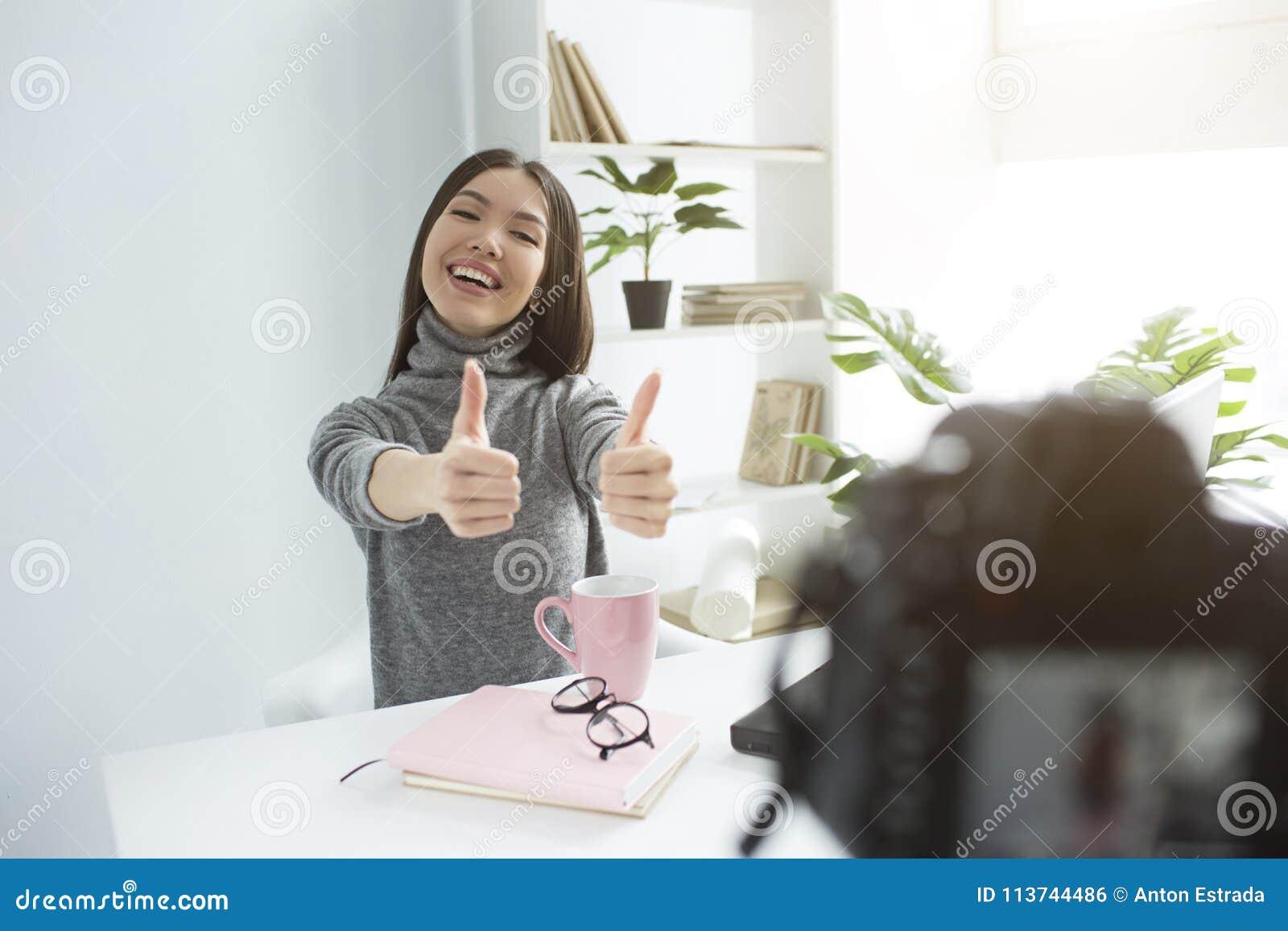 Uma imagem da menina feliz e do delightul que senta-se na tabela e que grava seu vlog novo Está mostrando-lhe os polegares grande