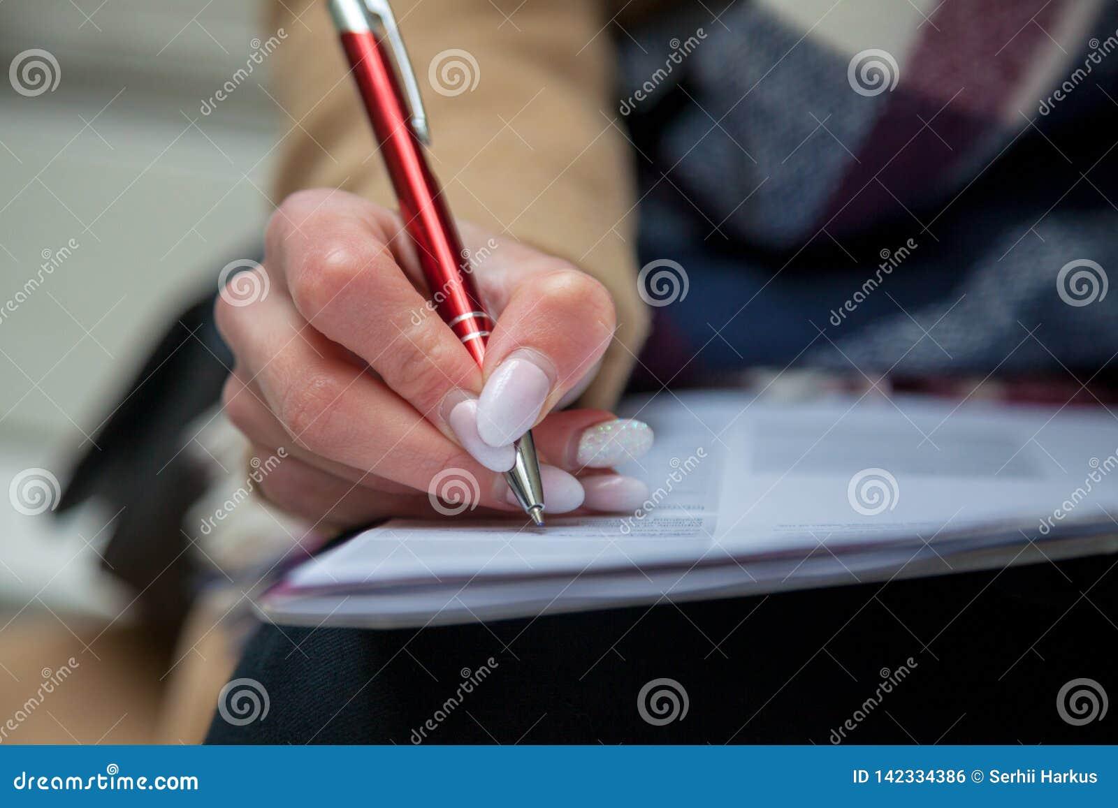 Uma imagem de uma mão e de uma pena que terminam um formulário