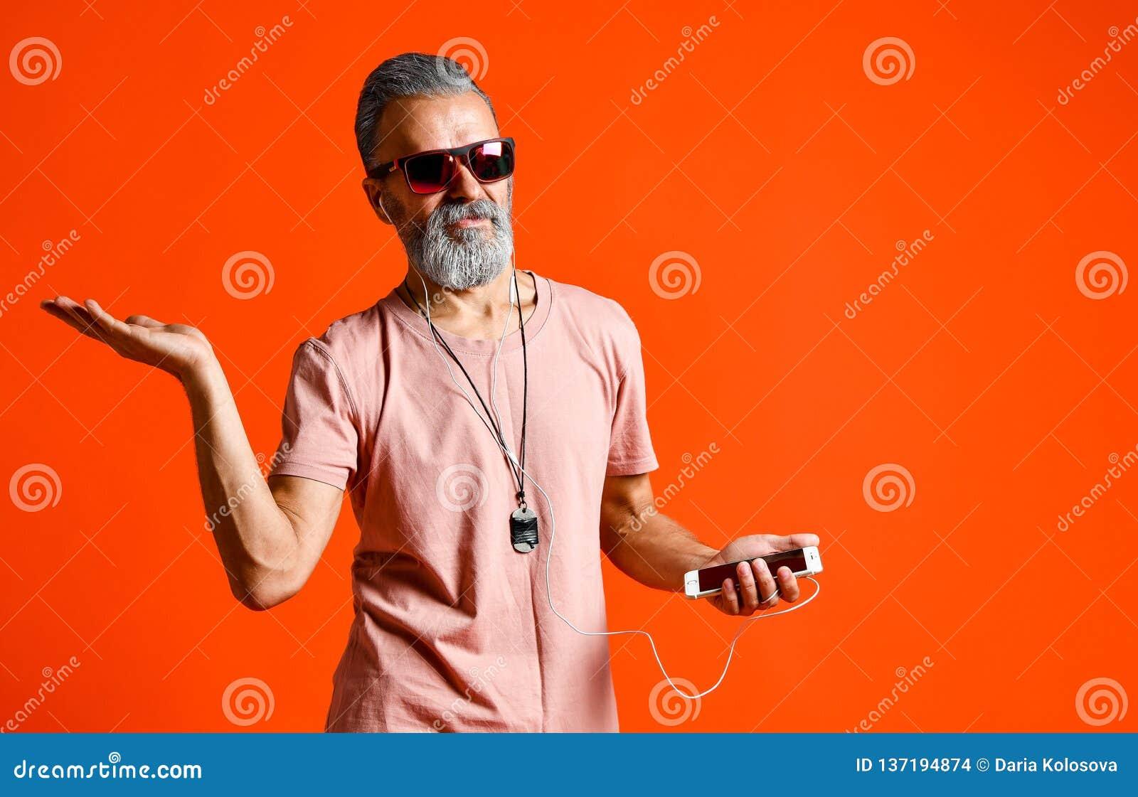 Uma imagem de um homem principal calvo idoso que escuta a música com fones de ouvido