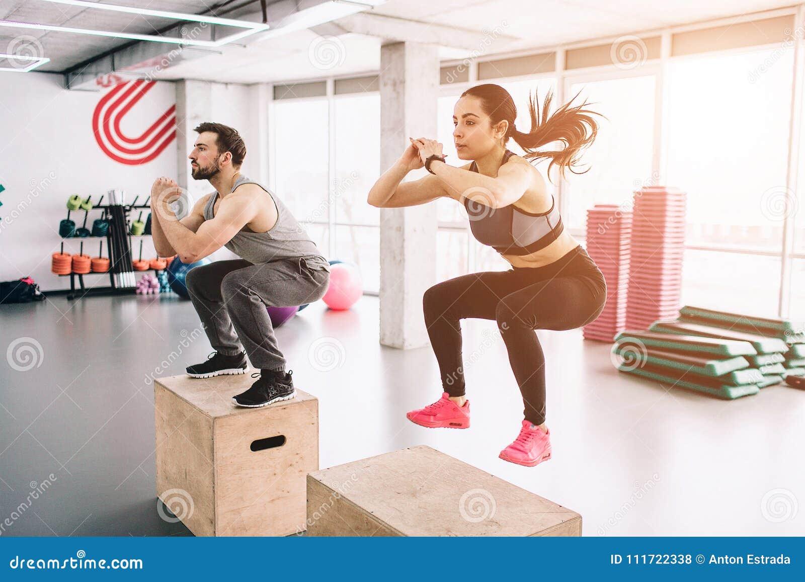 Uma imagem do homem novo magro e bem-construído e da mulher que fazem saltos na plataforma É um exercício duro mas estão fazendo